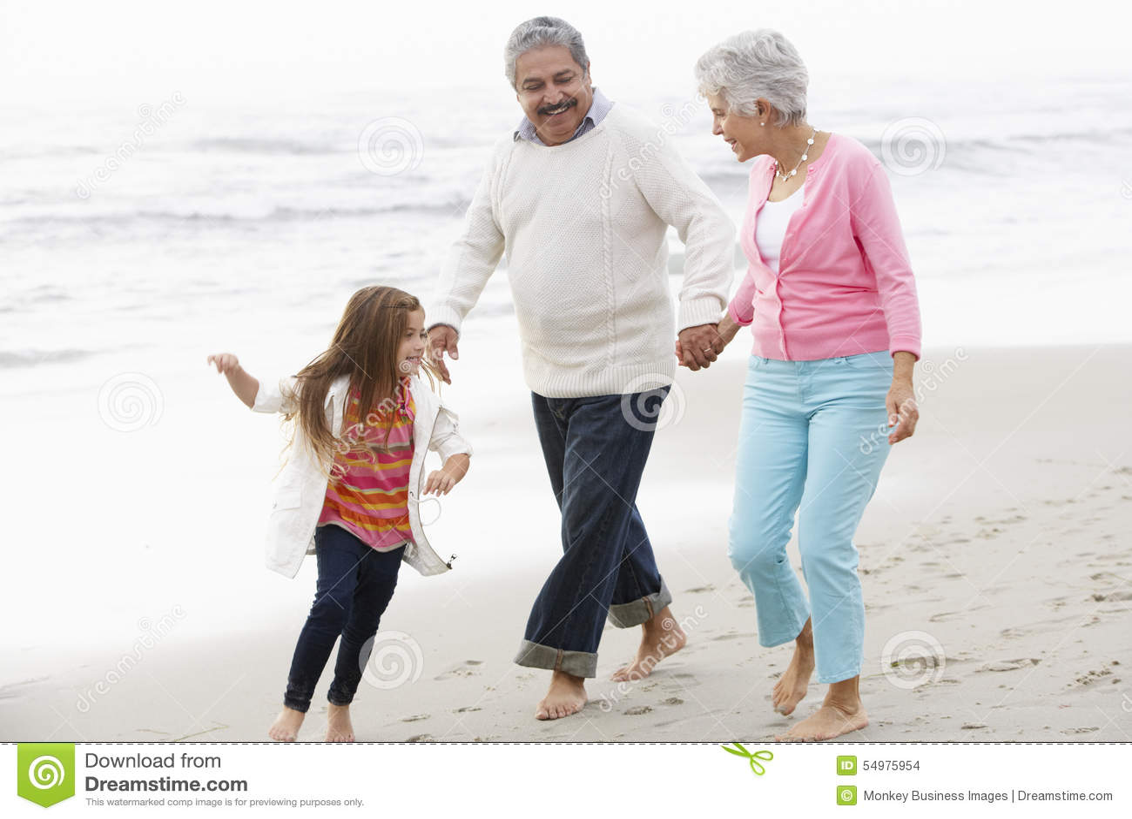 Morföräldrar som promenerar stranden med sondottern