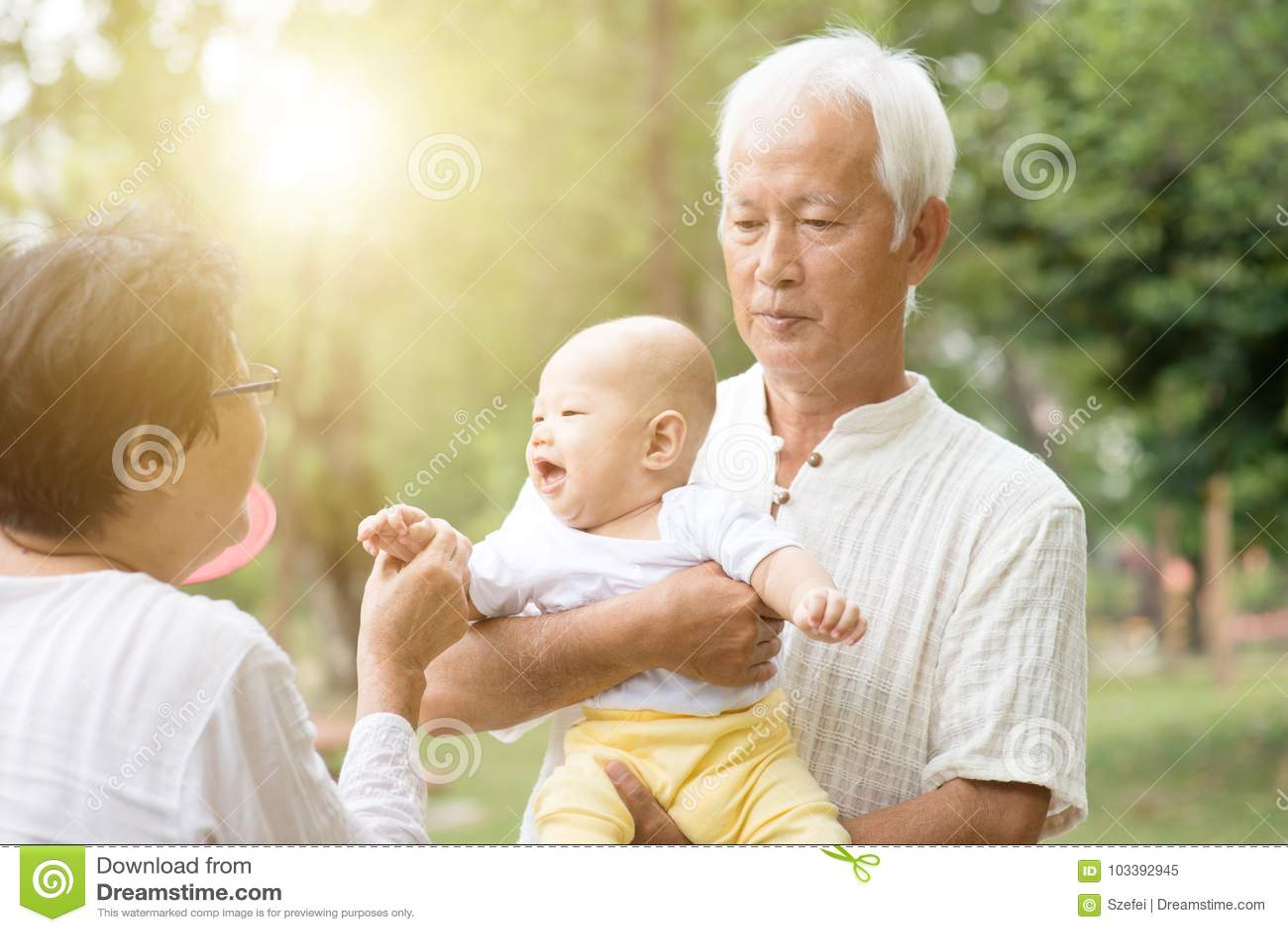 Morföräldrar som spelar med barnbarnet utomhus