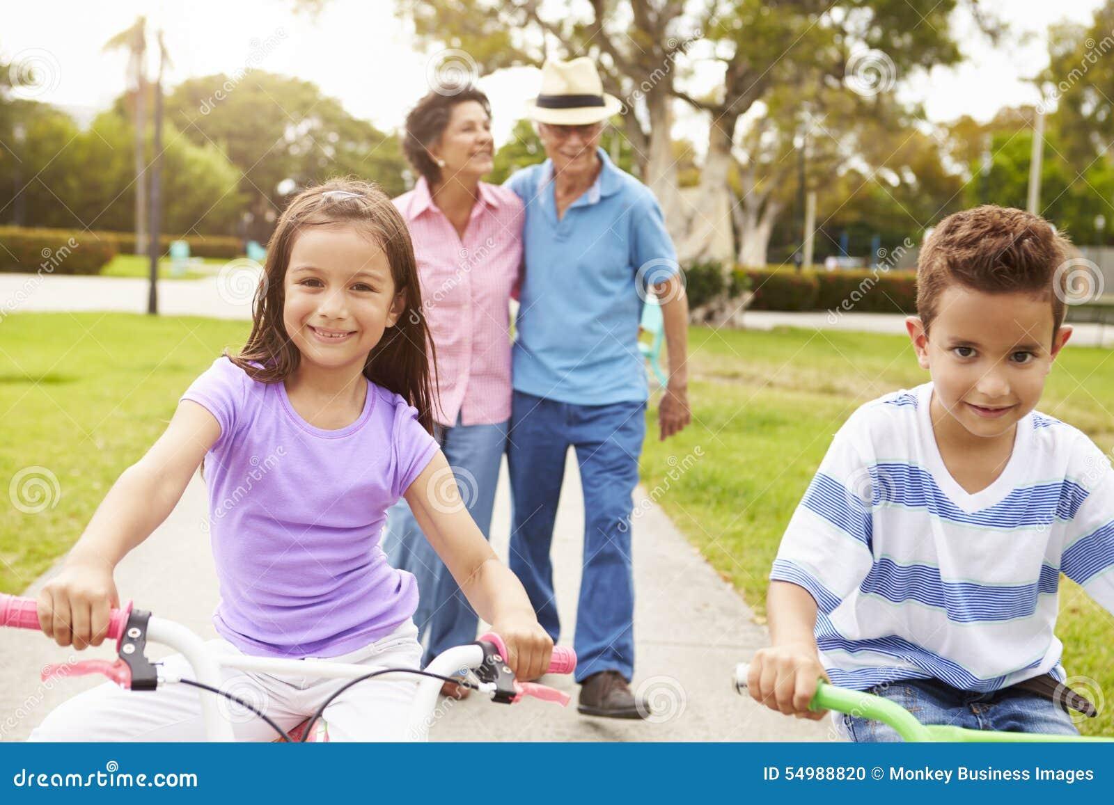 Morföräldrar som tar barnbarn till ritten, cyklar parkerar in