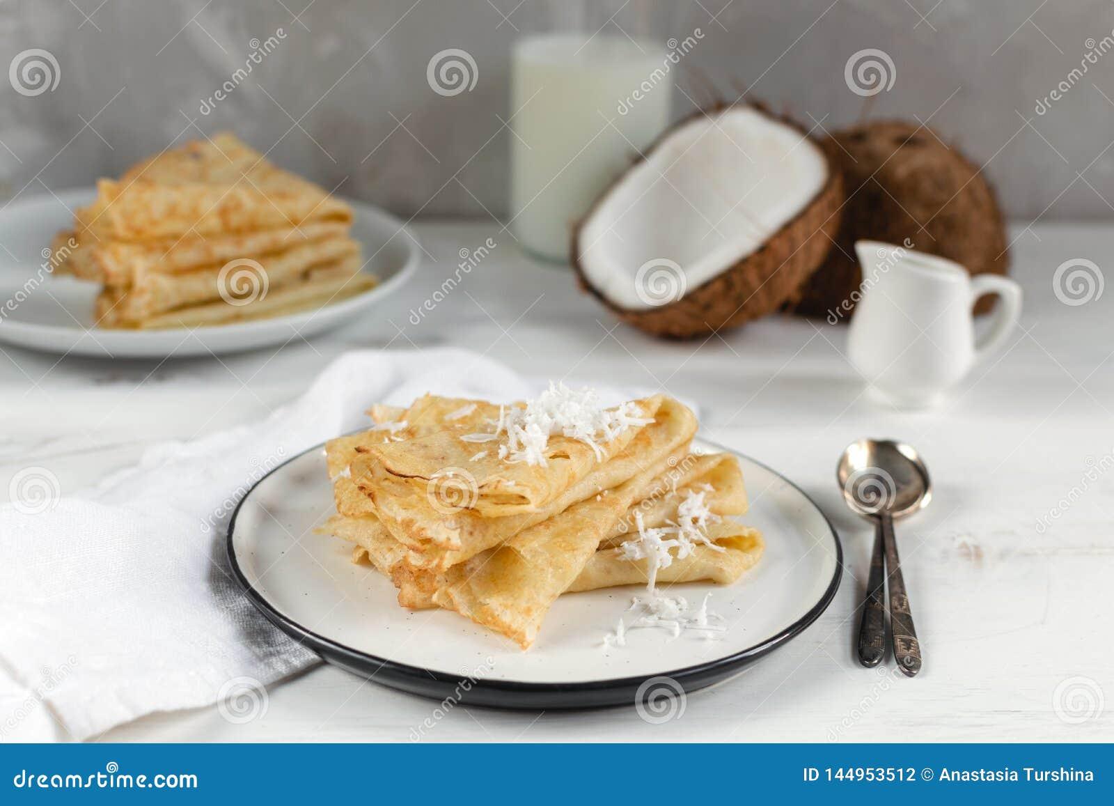 Morgen, Frühstück - traditionelle russische Blinipfannkuchen, französische Krepps, frische Kokosnuss, Milchflasche, weißer ke