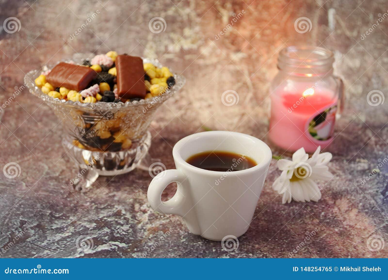 Morgenkaffee in Eile: ein Tasse Kaffee, Blumen in einem Vase, Trockenfr?chte und Bonbons in einem Vase, eine brennende Kerze