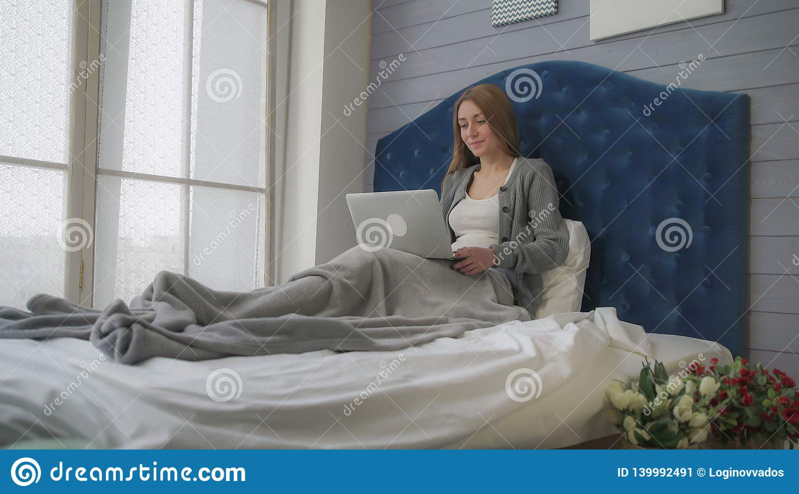 Morgenreise, Mädchen im Bett sprechend mit einem Laptop