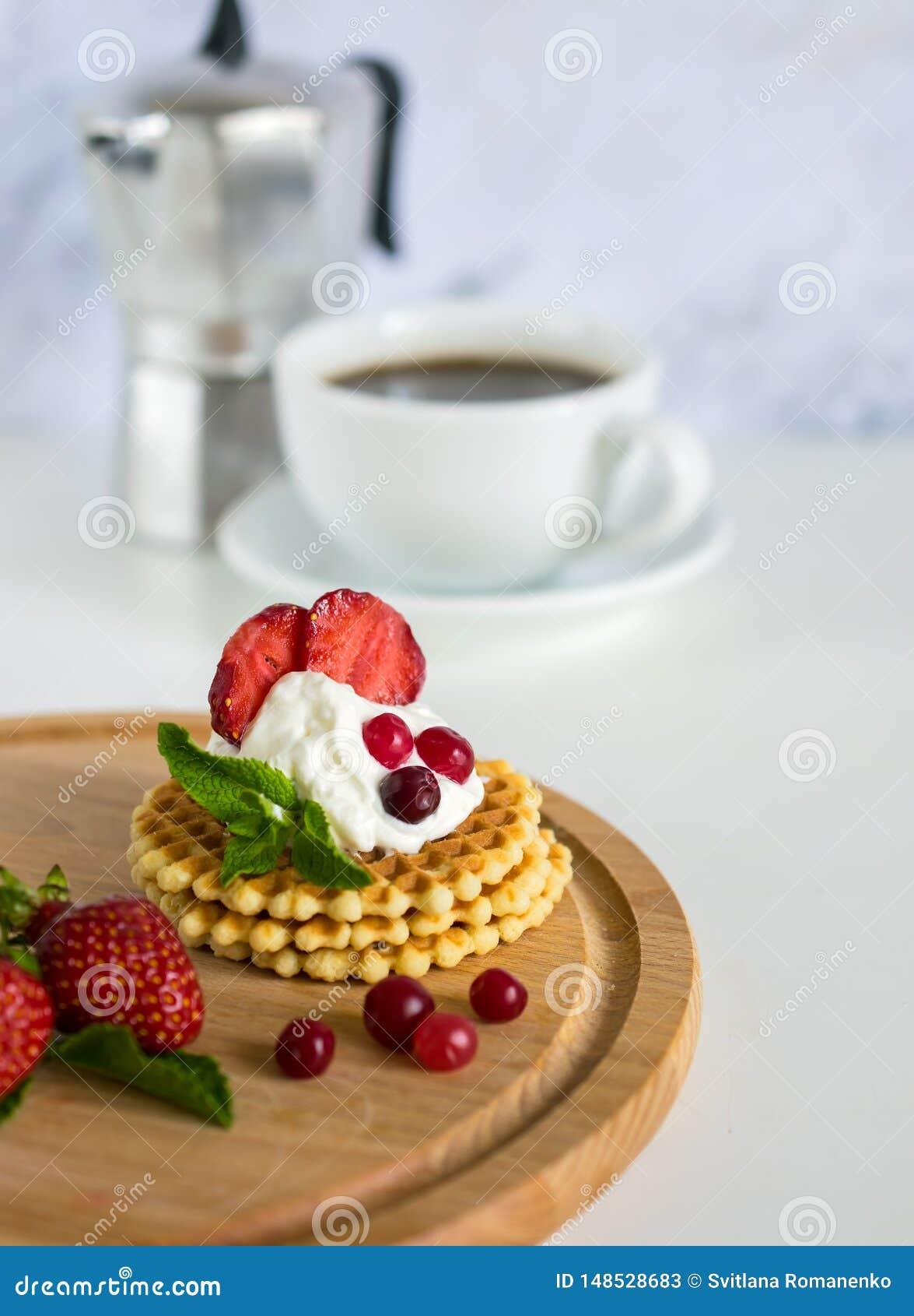 Morgonfrukost med kaffe och frasiga belgiska dillandear med piskade kr?m och jordgubbar