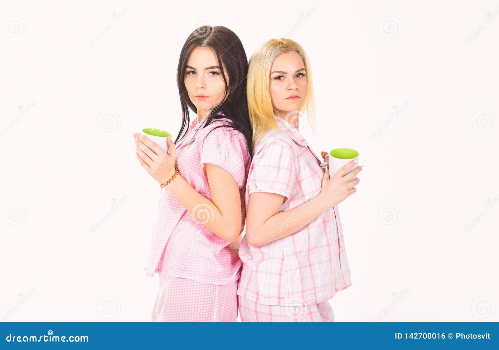 Morgonkaffebegrepp Blondinen och brunetten på sömniga framsidahåll rånar med kaffe Systrar eller bästa vän i pyjamas