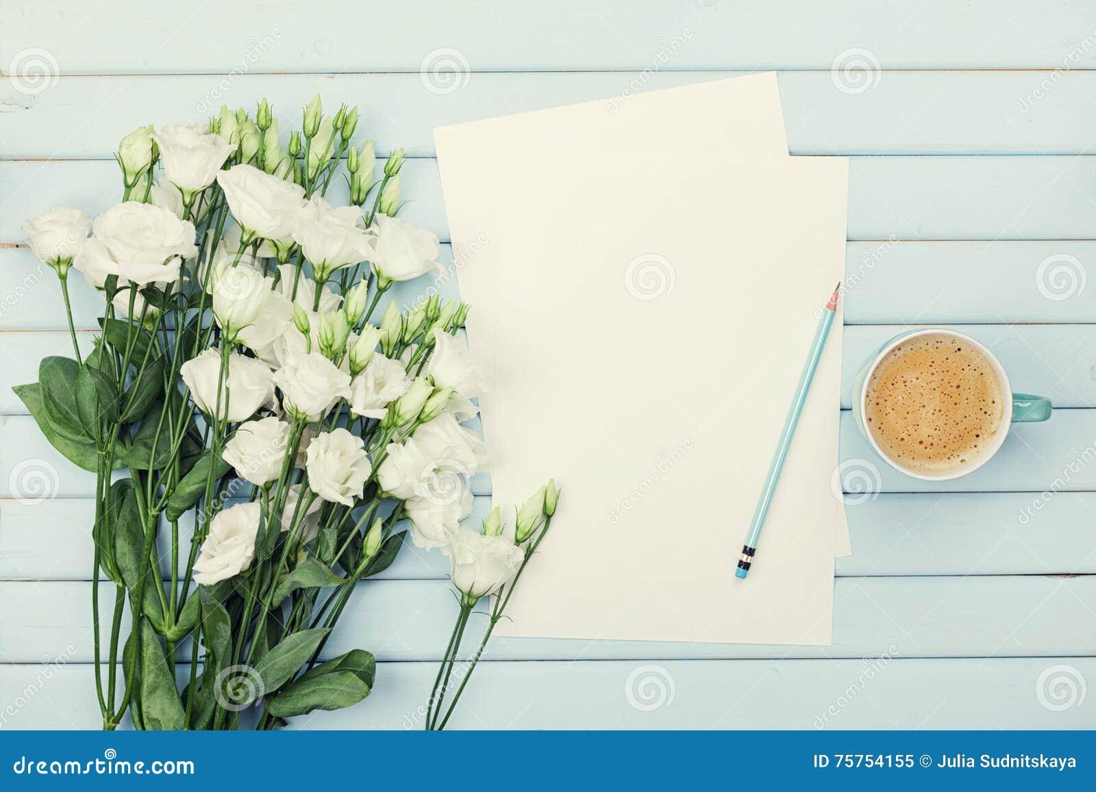 Morgonkaffekopp, tom pappers- lista, blyertspenna och bukett av eustomaen för vita blommor på den blåa lantliga tabellen från öve