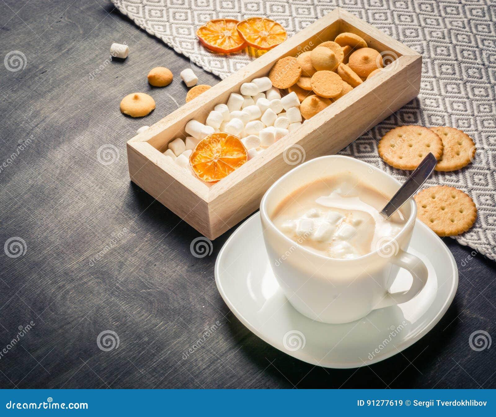 Morgonkakao med marshmallower, kakor och mjölkar i träask mörkt trä för bakgrund