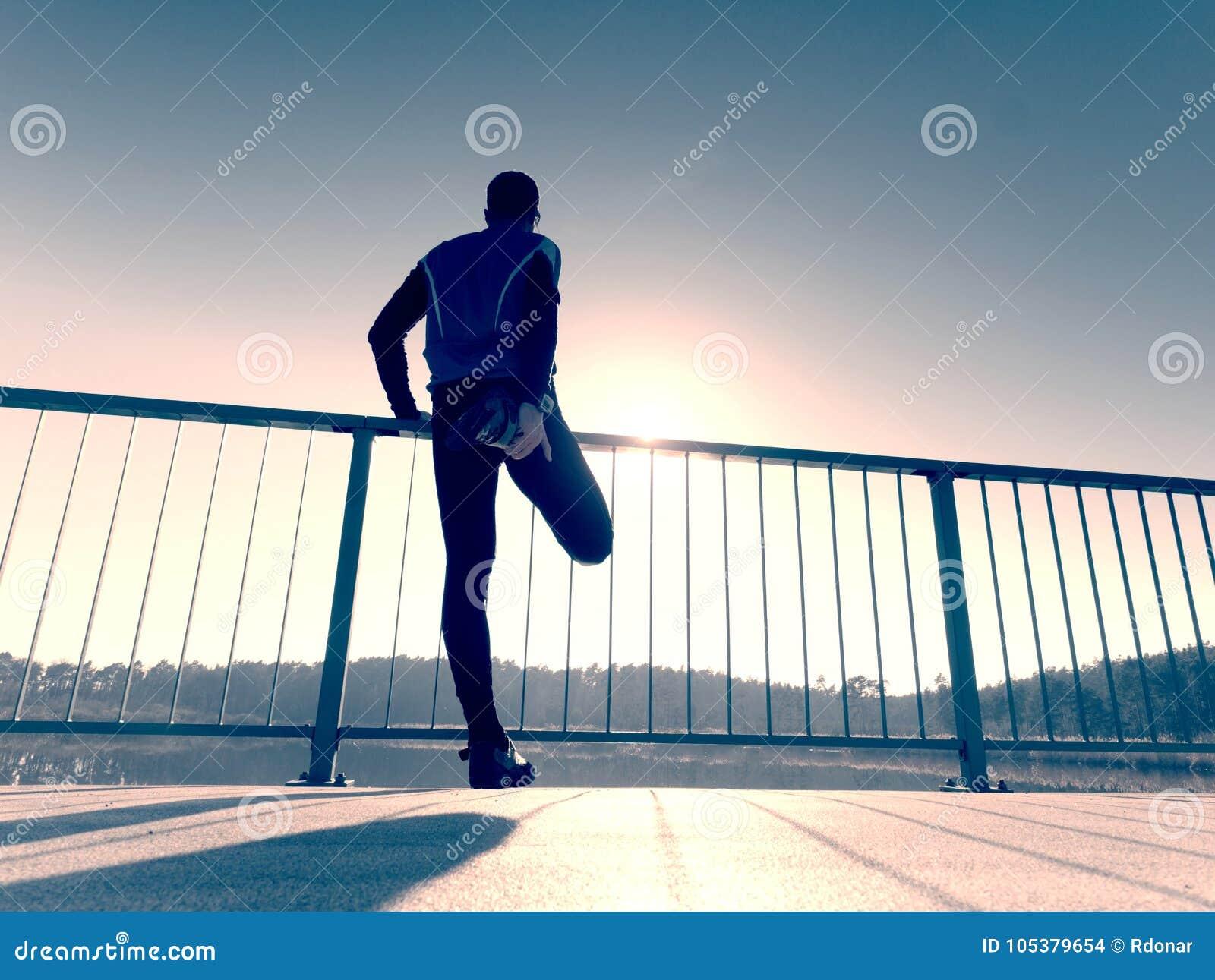 Morgonlöparen i högväxt svart damasker gör kroppen som sträcker på brobanan Utomhus- öva