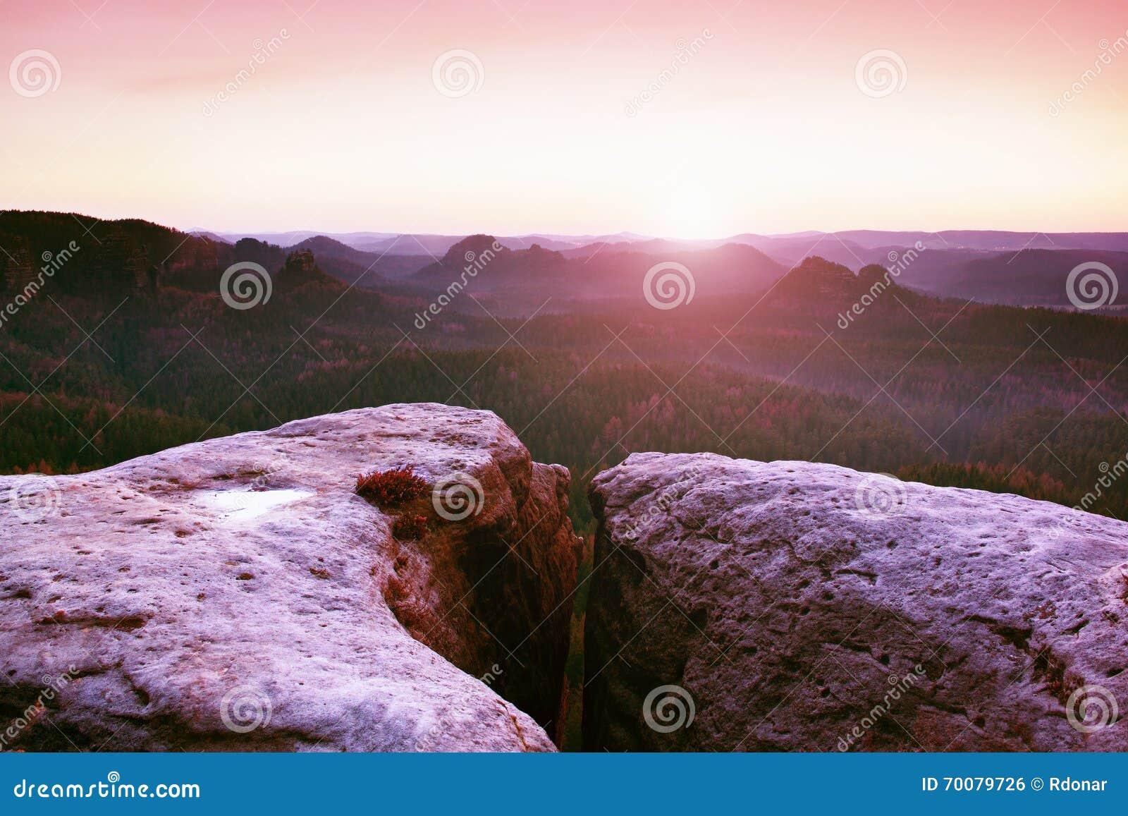 Morgonsikt över sandstenklippan in i skogdalen, gryningsol på horisonten