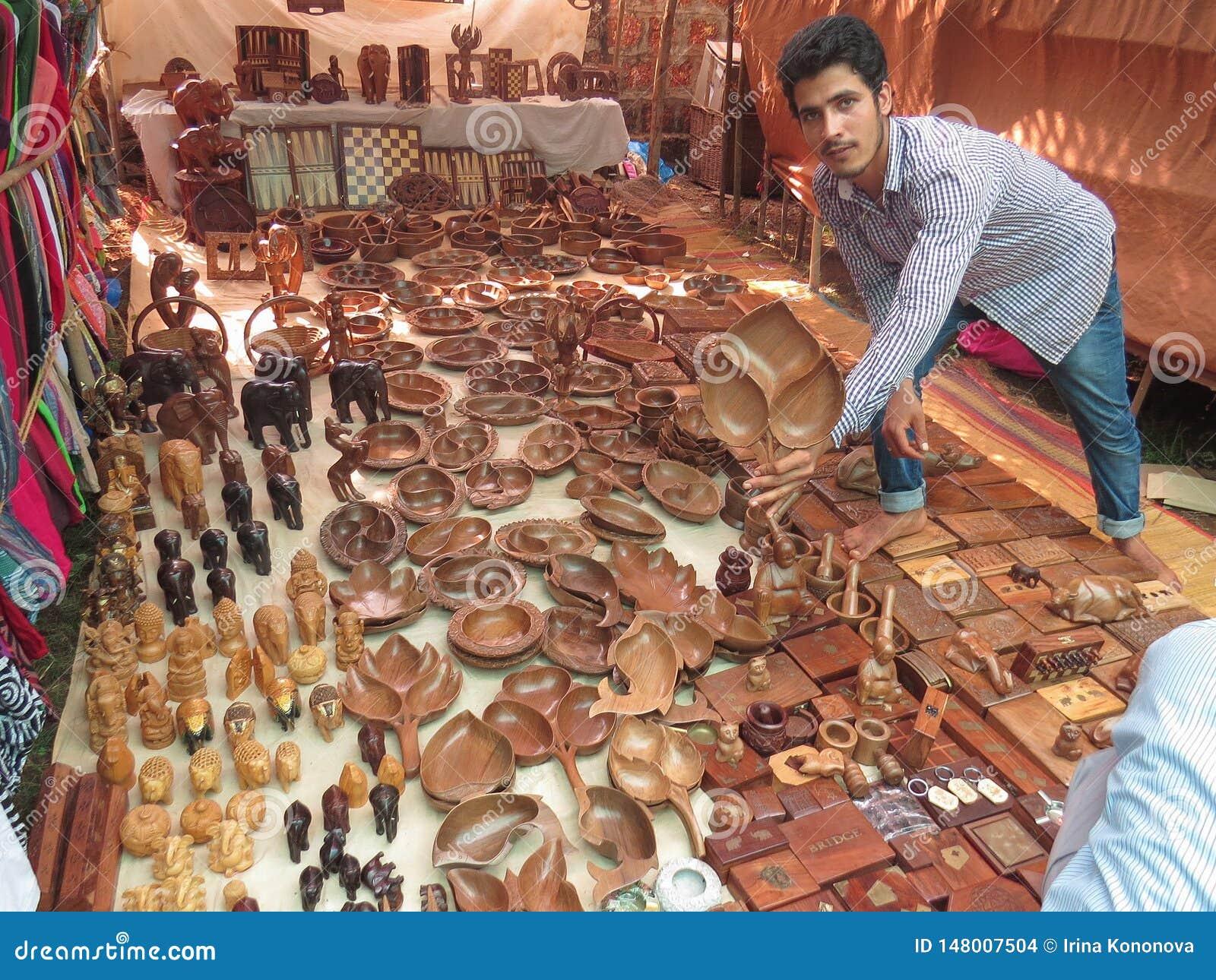 Morjim, Índia, o 23 de novembro de 2013 No mercado, nas mostras indianas e nas ofertas de um homem para comprar uma placa de made