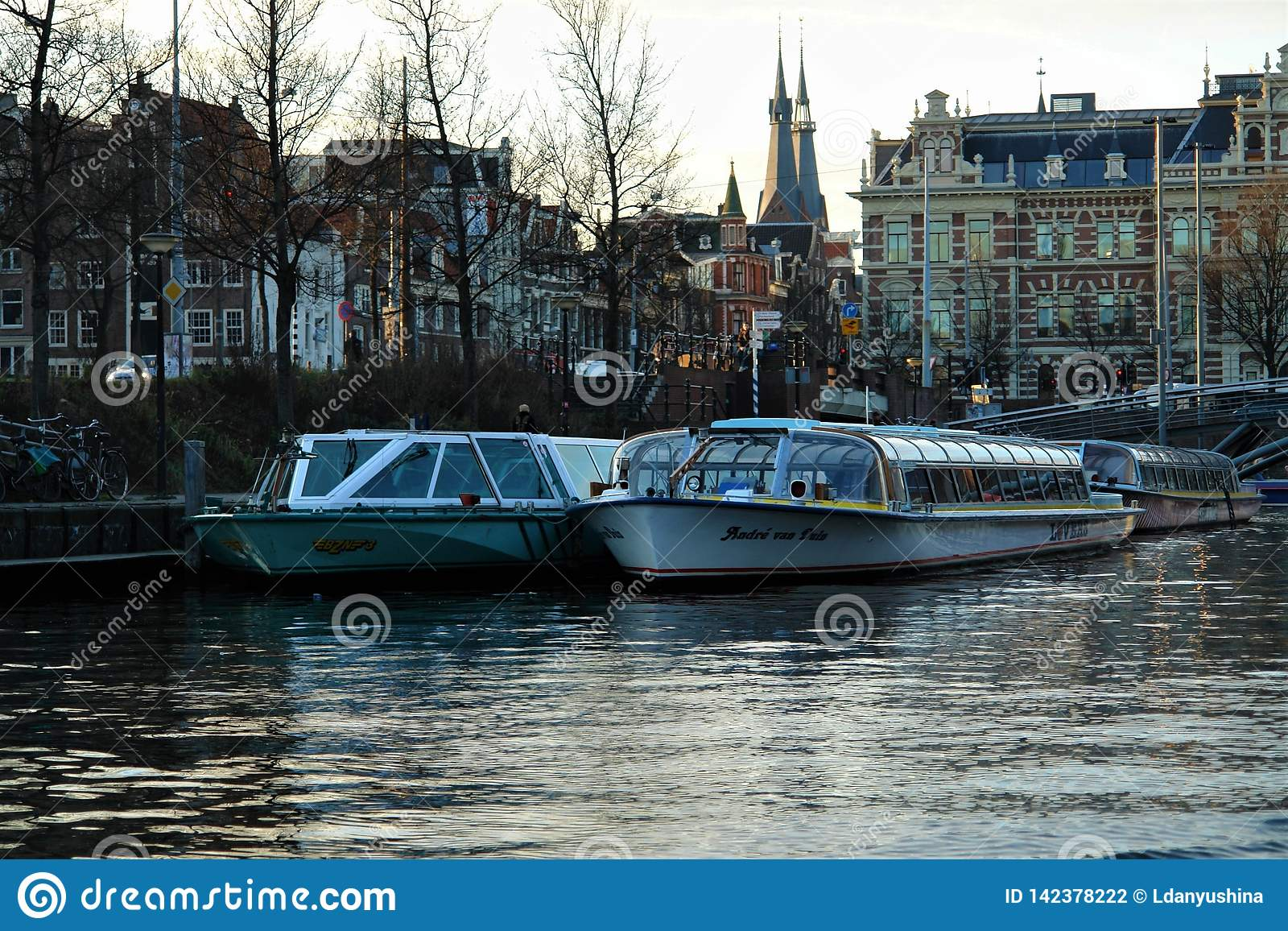 Morning in Amsterdam. Water street with boats on the pier, reflected in quiet water.