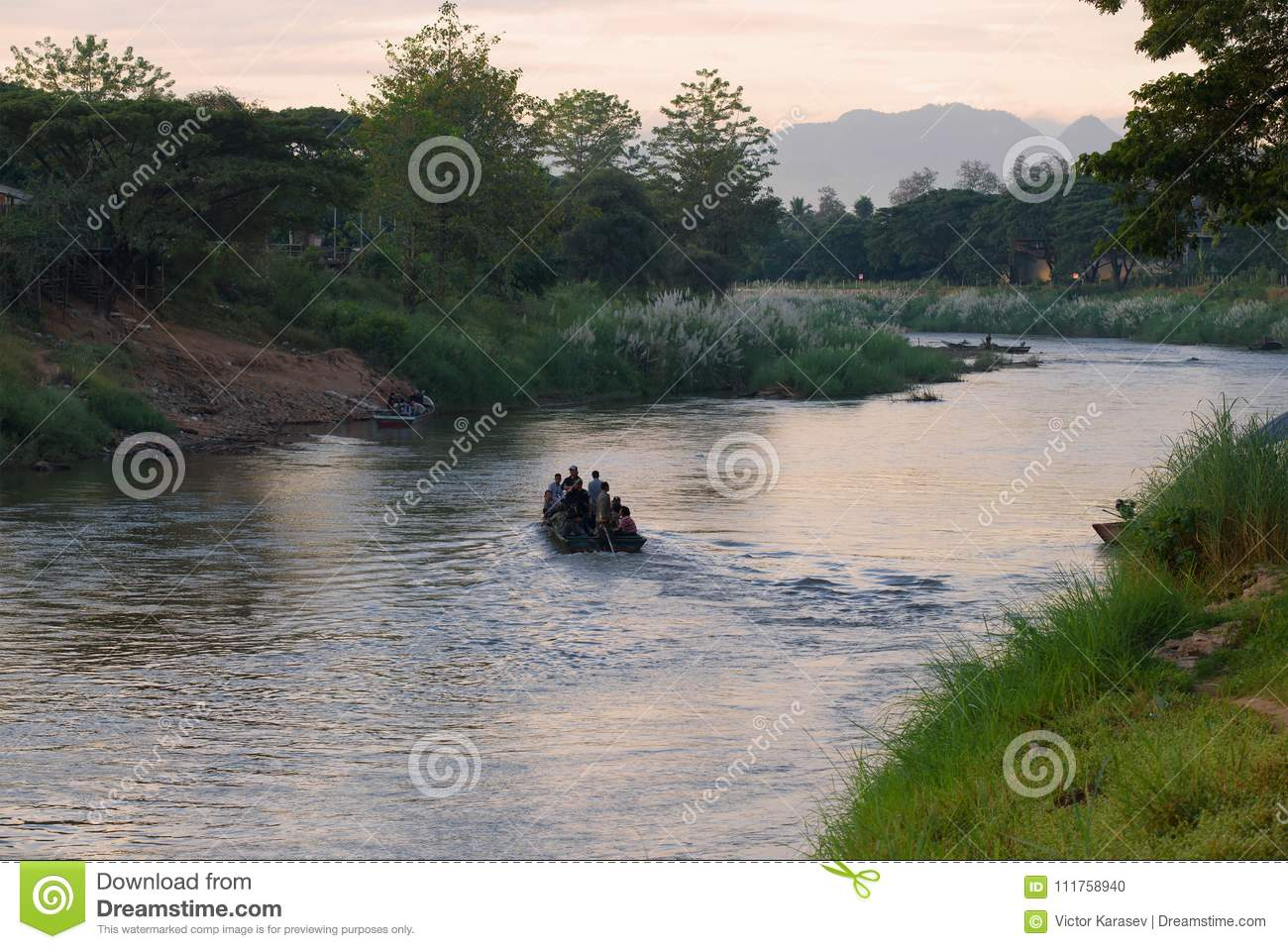 Morning on the boundary Menammey river. Burmans by the boat are illegally transported on the Thai side, Myanmar