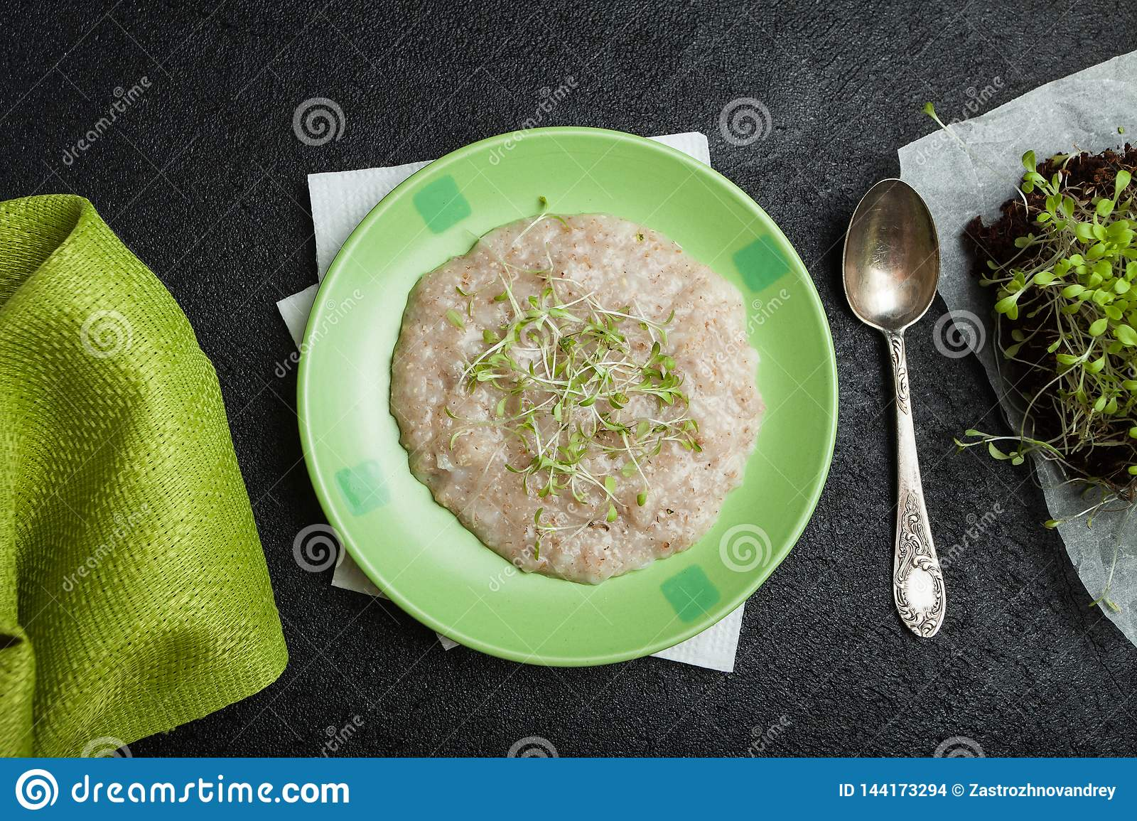 Morning breakfast, organic oatmeal with micro greens on a black background. A towel, a vintage spoon and young salad sprouts