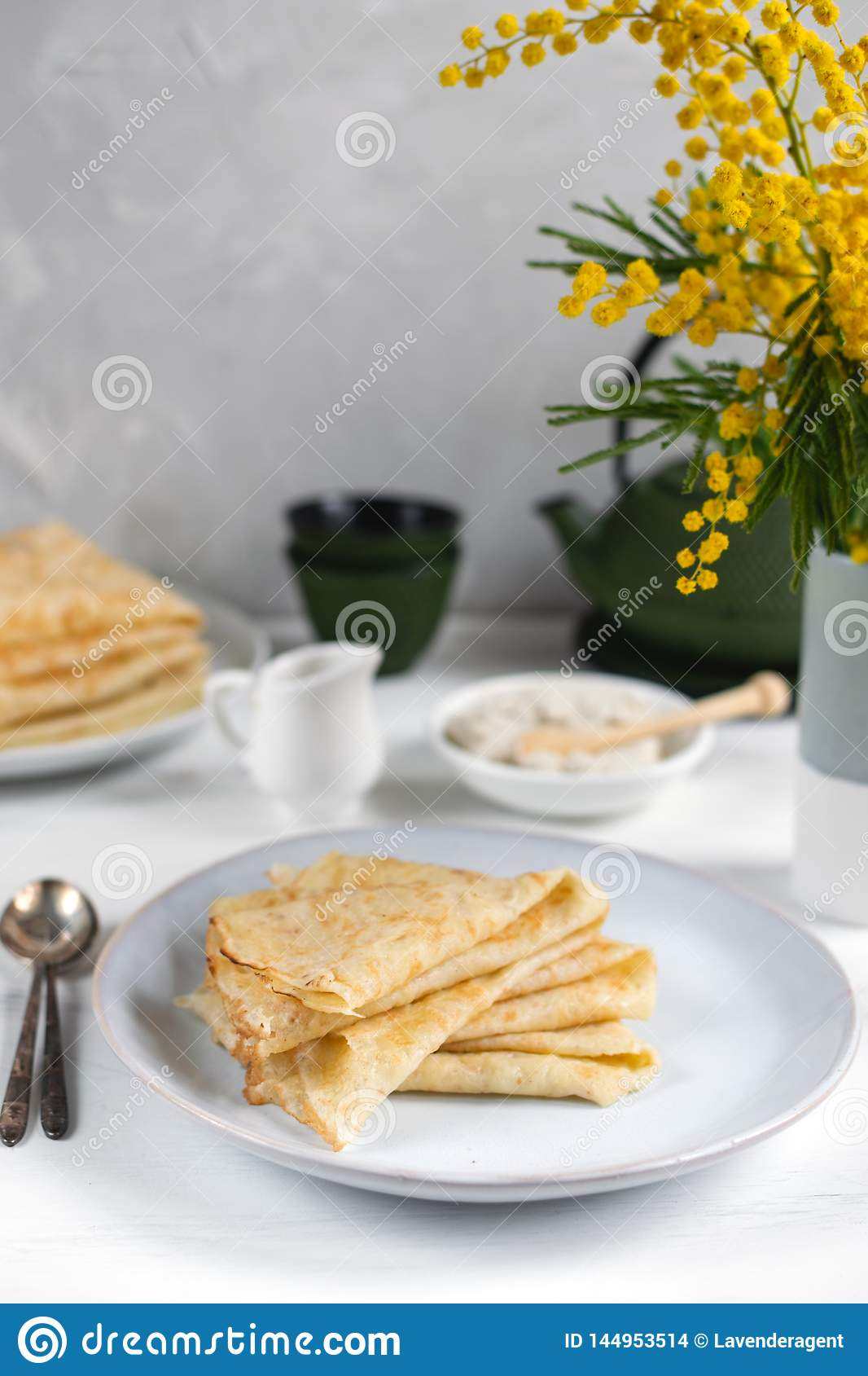 Morning, breakfast - traditional russian blini pancakes, french crepes whipped cream, cast iron green teapot, mimosa flower