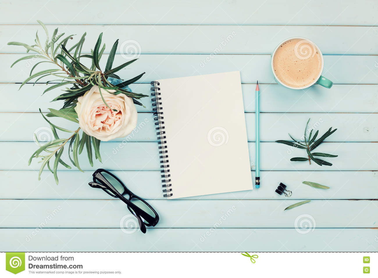 Morning coffee cup, clean notebook, pencil, eyeglasses and vintage rose flower in vase on blue rustic table top view. Flat lay.