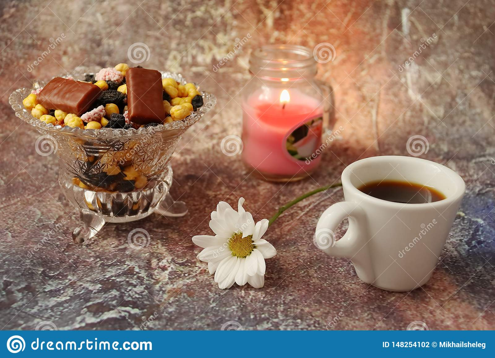 Morning coffee in a hurry: a cup of coffee, flowers in a vase, dried fruits and sweets in a vase, a burning candle