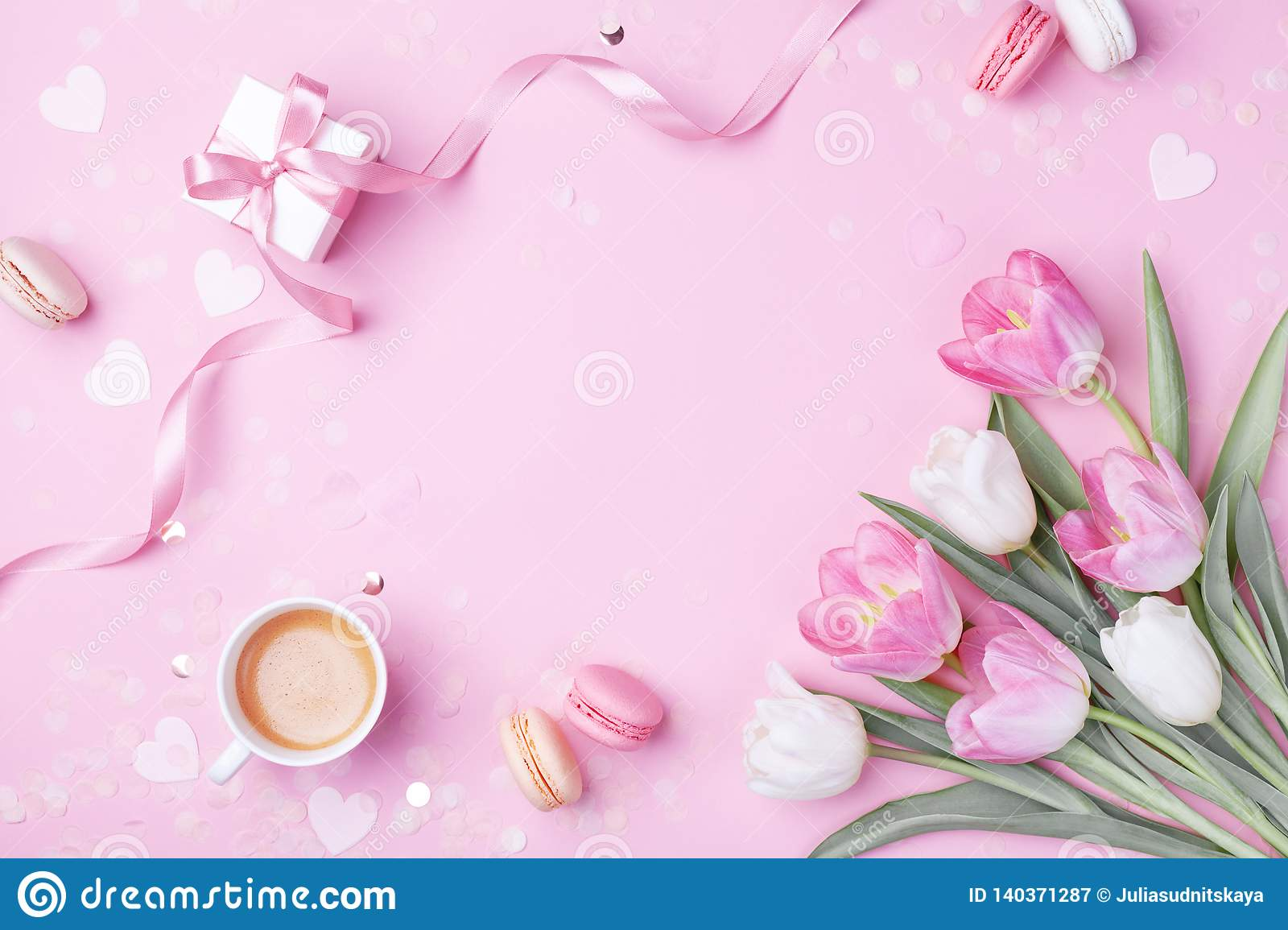 Morning cup of coffee, cake macaron, gift or present box and spring tulip flowers on pink. Breakfast for Women, Mother day
