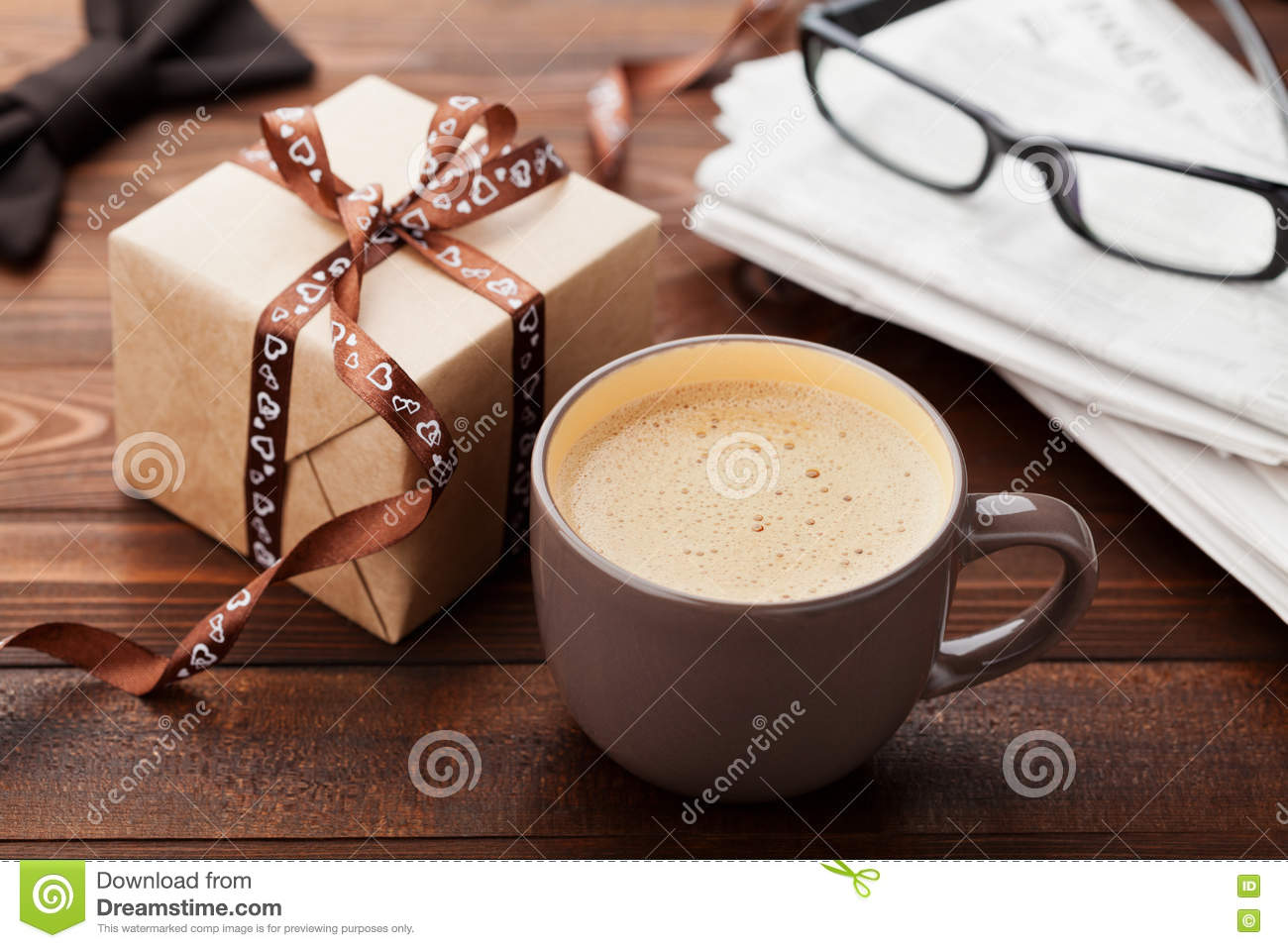 Morning cup of coffee, gift, newspaper, glasses and bowtie on wooden desk for breakfast on Happy Fathers Day