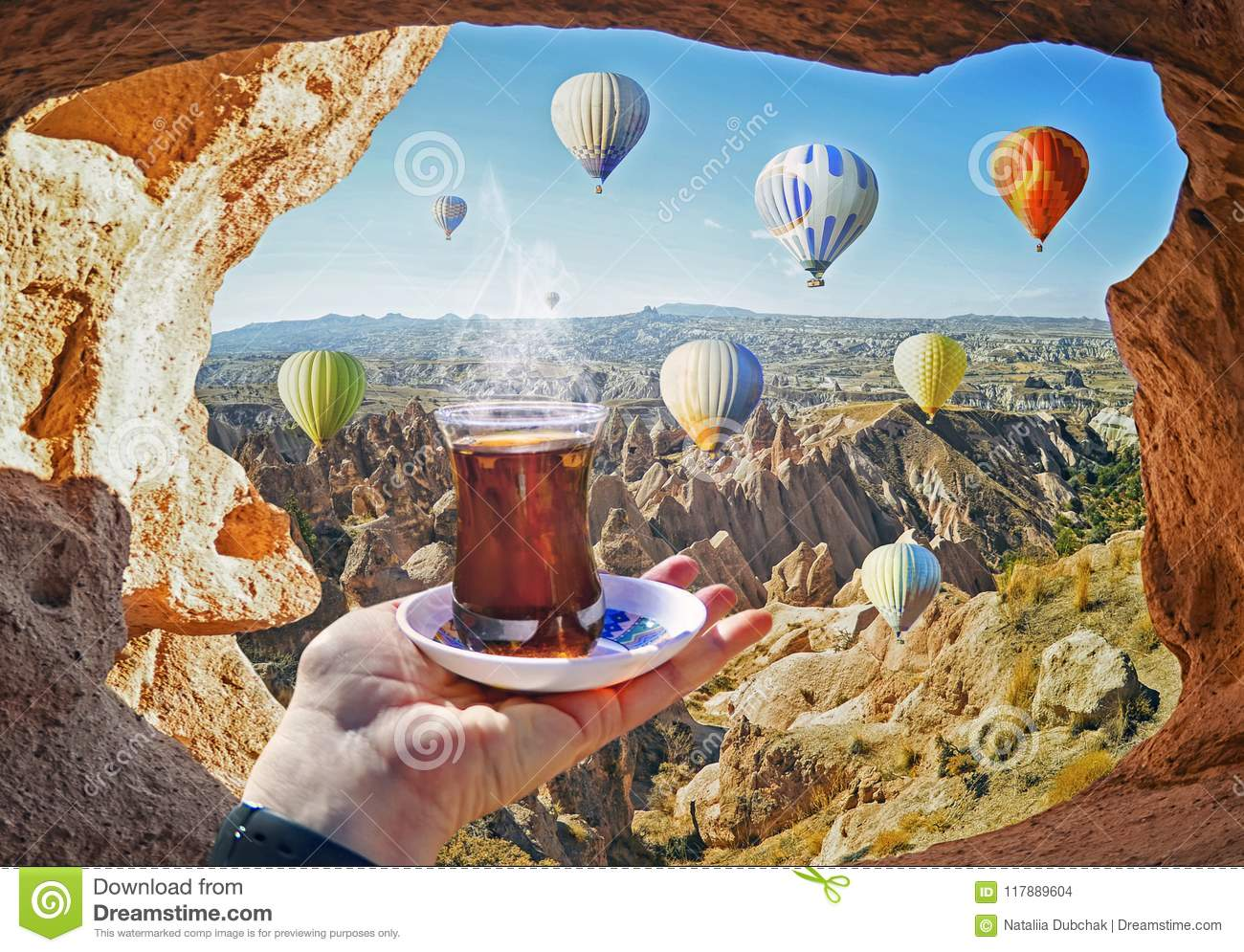 Morning cup of tea with view of colorful hot air balloons