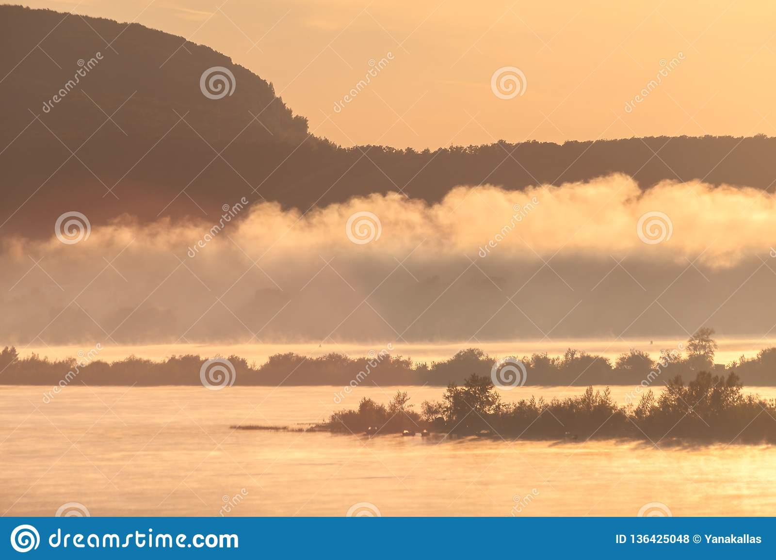 Morning fog rises over the river in the light of the rising sun against the silhouettes of mountains and Islands