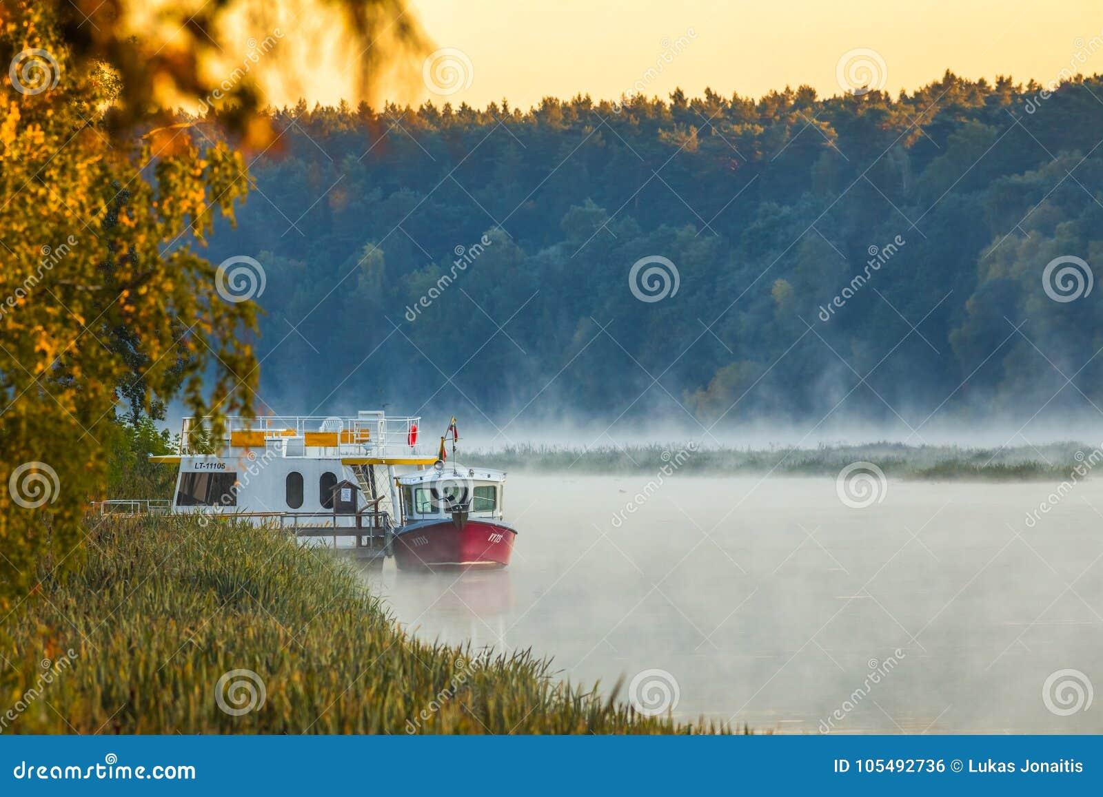 Morning foggy landscape of boats in Nemunas river