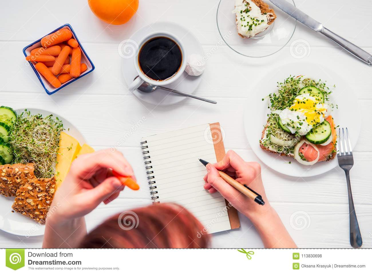 Morning habits of successful people. Day planning and healthy meal. Woman eating carrot and writing in notebook on the served for