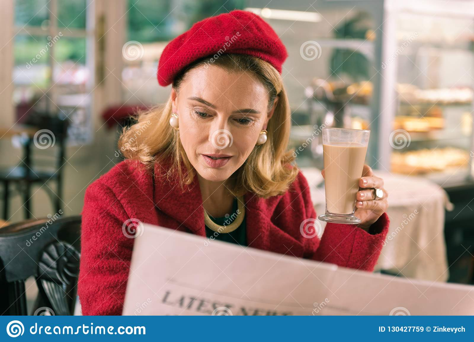 108f71f2452a Mature French Woman Reading Morning Newspaper Sitting In Bakery ...