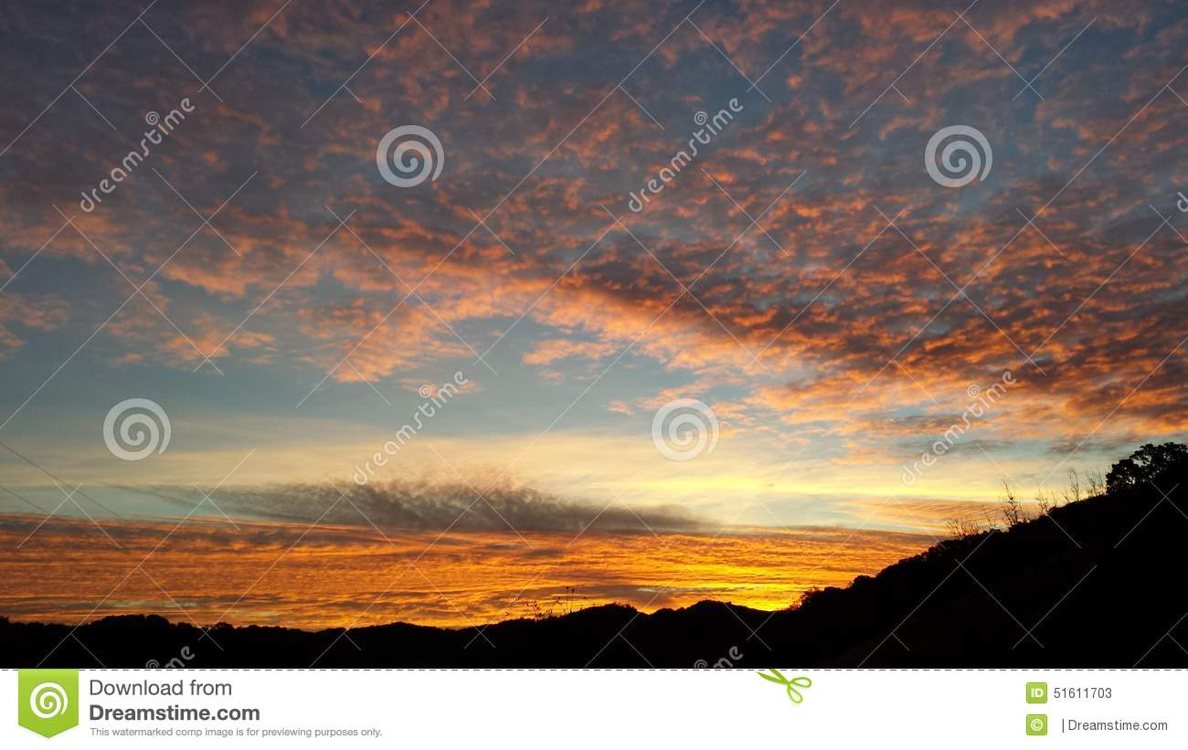 Sunrise filling the sky with colors - blue orange pink red grey clouds