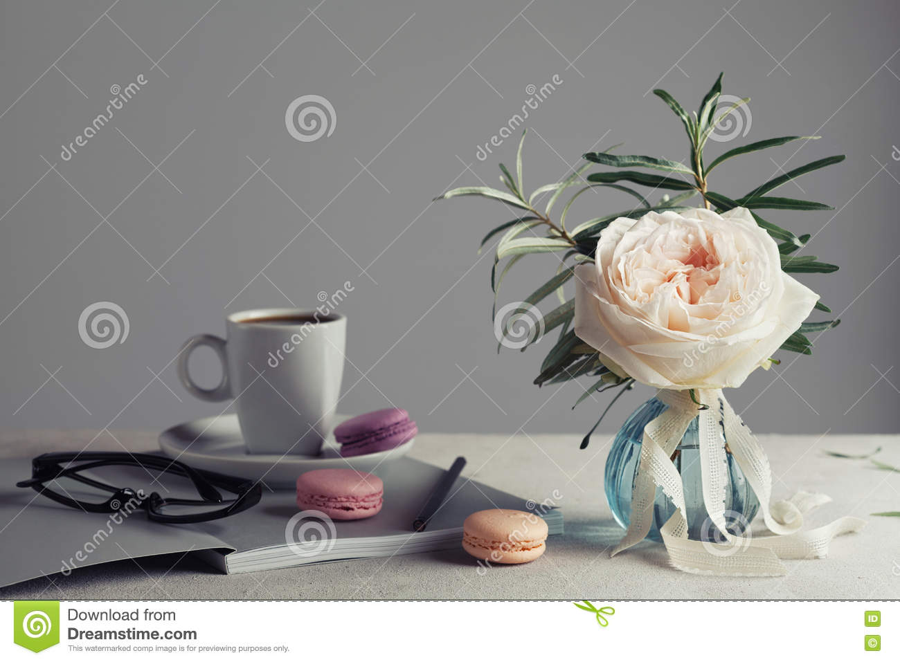 Morning still life with vintage rose in a vase, coffee and macarons on a light table. Beautiful and cozy breakfast.