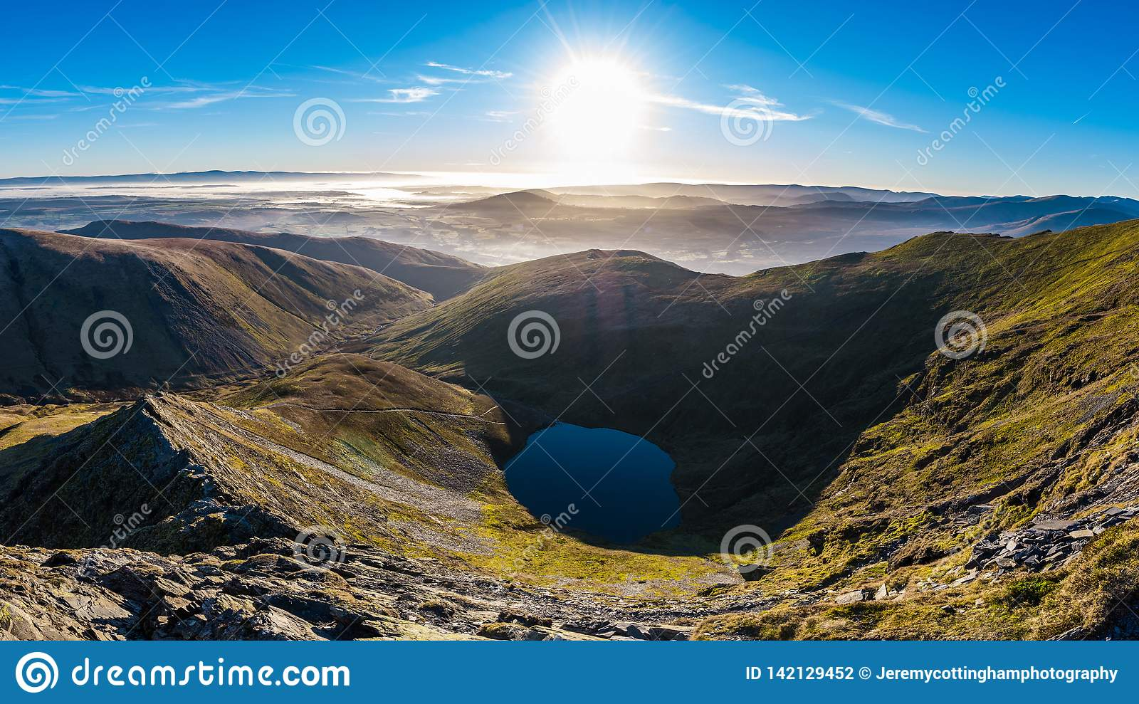 Morning view from Sharp Edge on Blencathra, Lake District, Cumbria with lake tarn and cloud inversion over mountains in the
