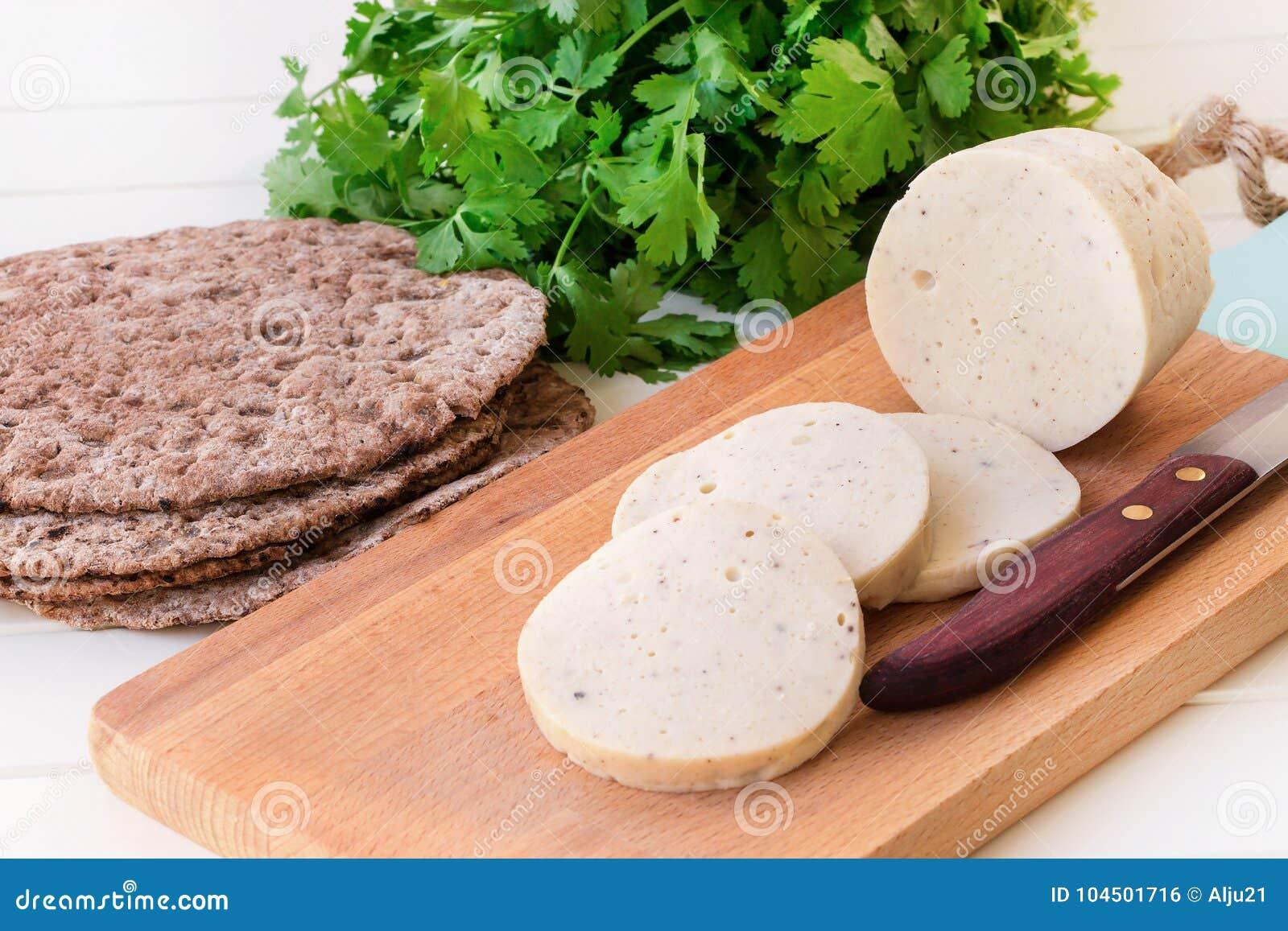 Mortadella fervido caseiro dietético da salsicha do peito de frango com especiarias em uma placa de corte de madeira Plano multic