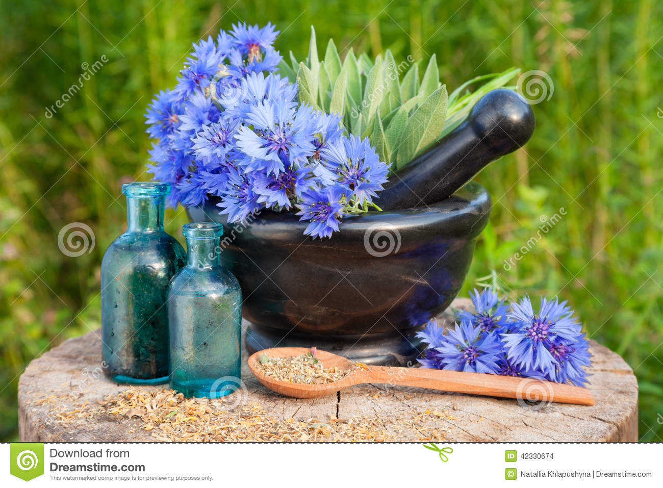 Mortar with blue cornflowers and sage, vials with essential oil