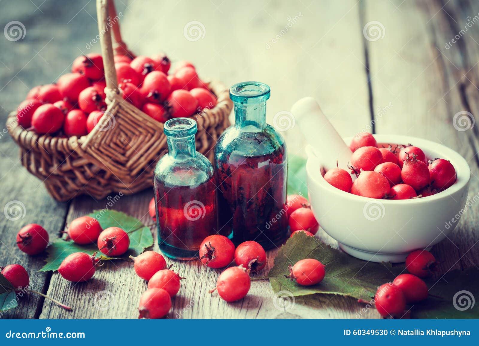Mortel av hagtornbär, tinkturflaskor och taggäpplet i korg