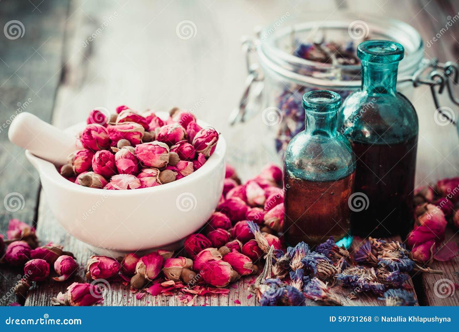 Mortero con los brotes color de rosa, las botellas de tinte y las flores secadas