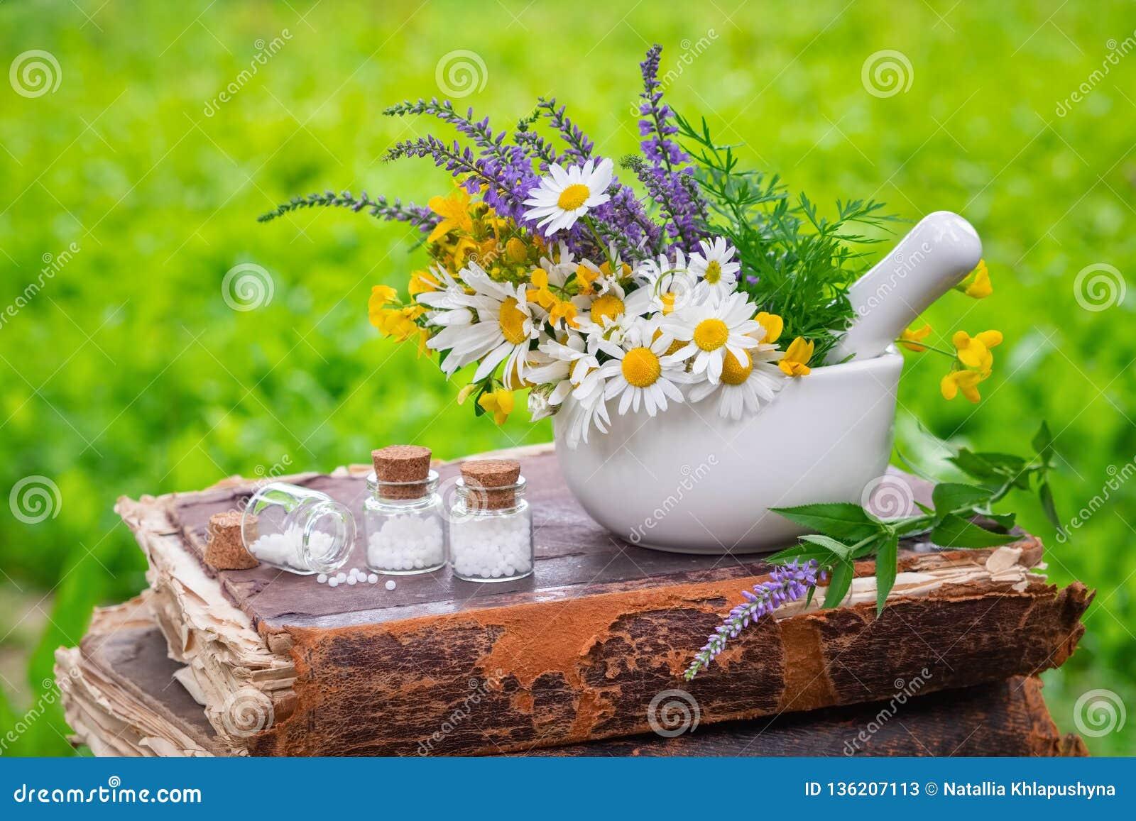 Mortier van in openlucht het helen van kruiden, flessen van homeopathische druppeltjes en oud boek