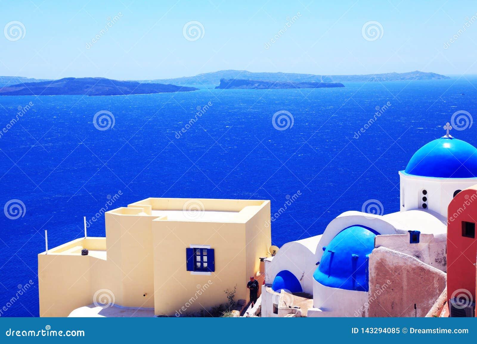 Morza i bielu domy z błękitnymi dachami Santorini