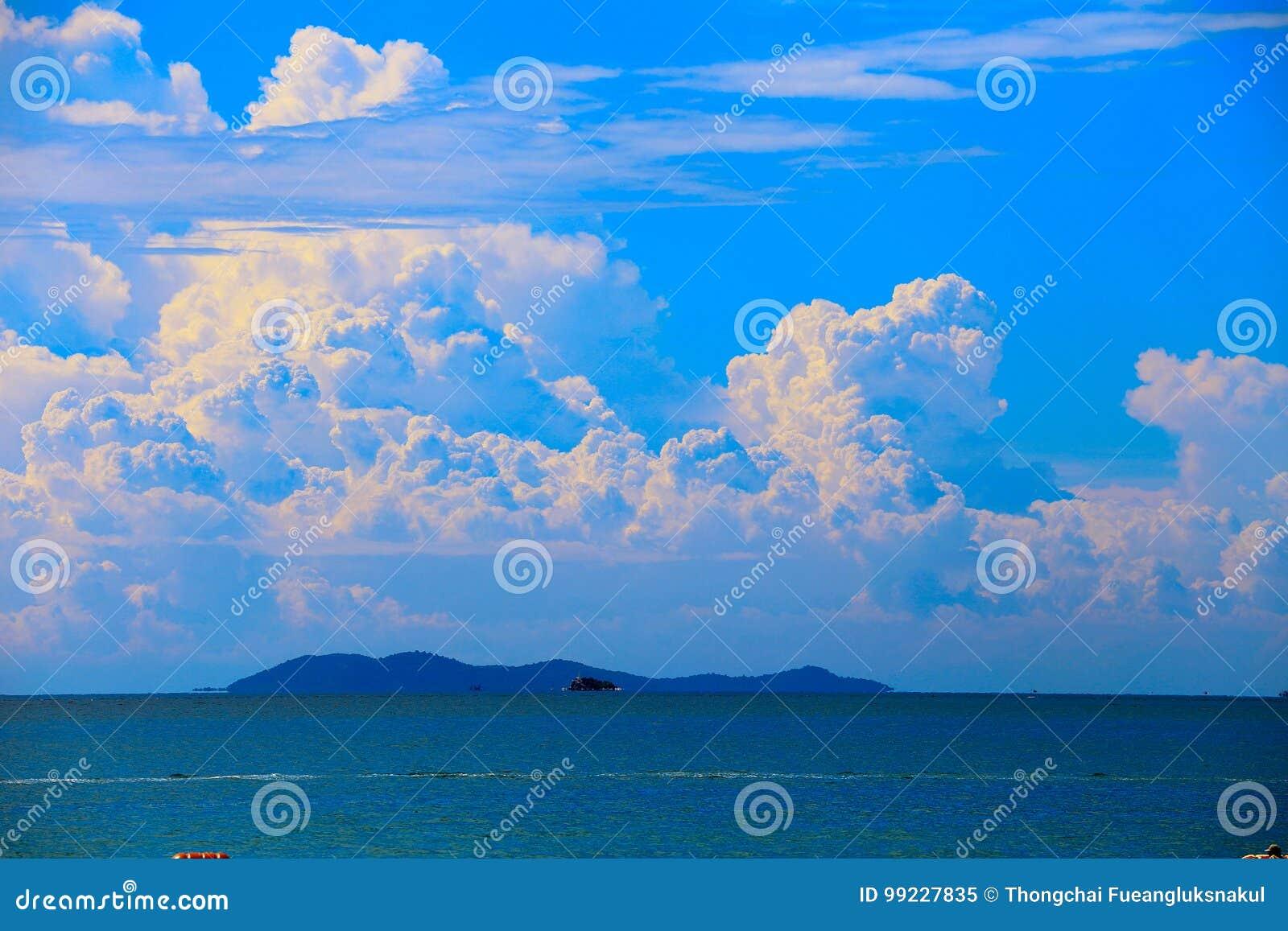 Morze z niebieskim niebem, chmura i góry, jako natura