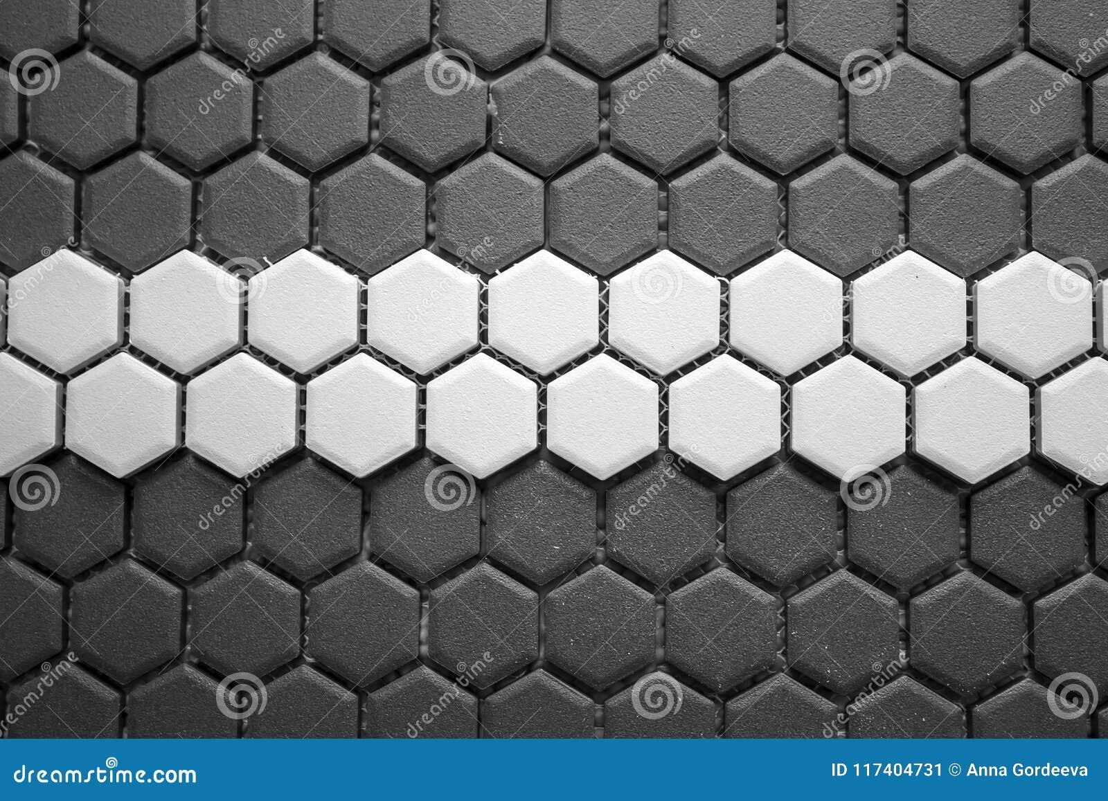 Mosaïque de carreaux de céramique faite de losanges gris avec une rayure blanche au milieu, sans jointoyer, maille-base et colle