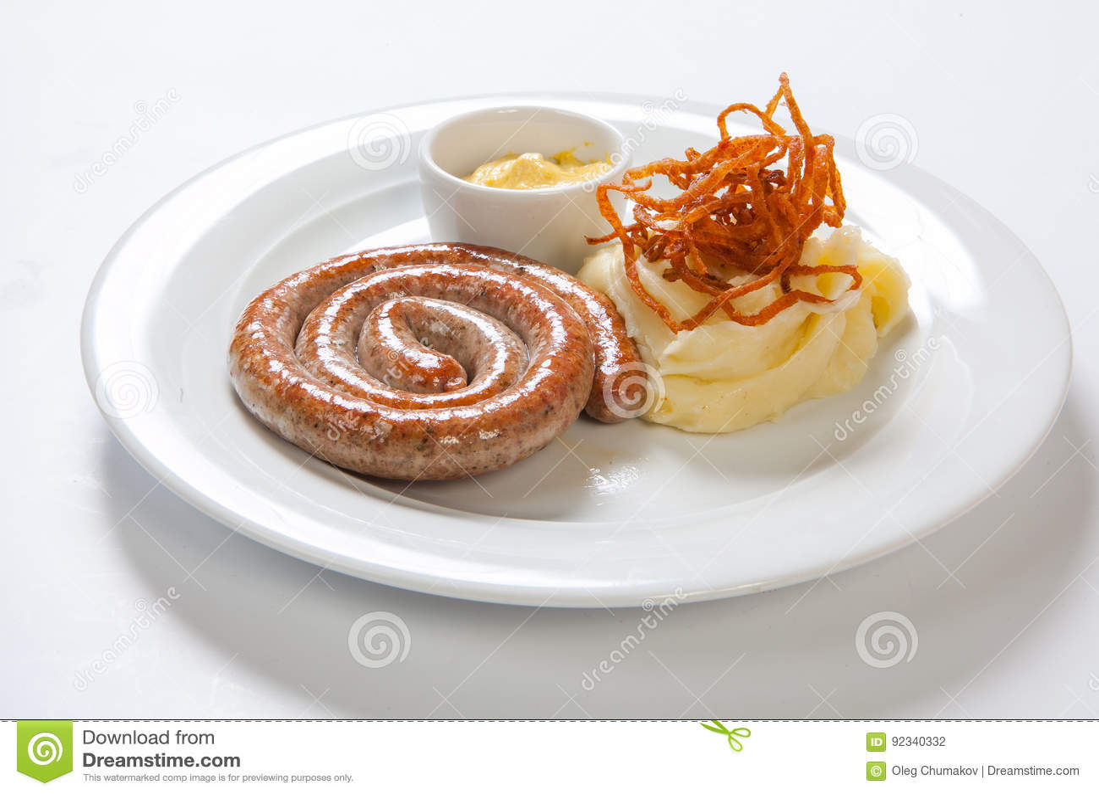 Mosad potatis och grillad korv eller bratwurst på den vita plattan