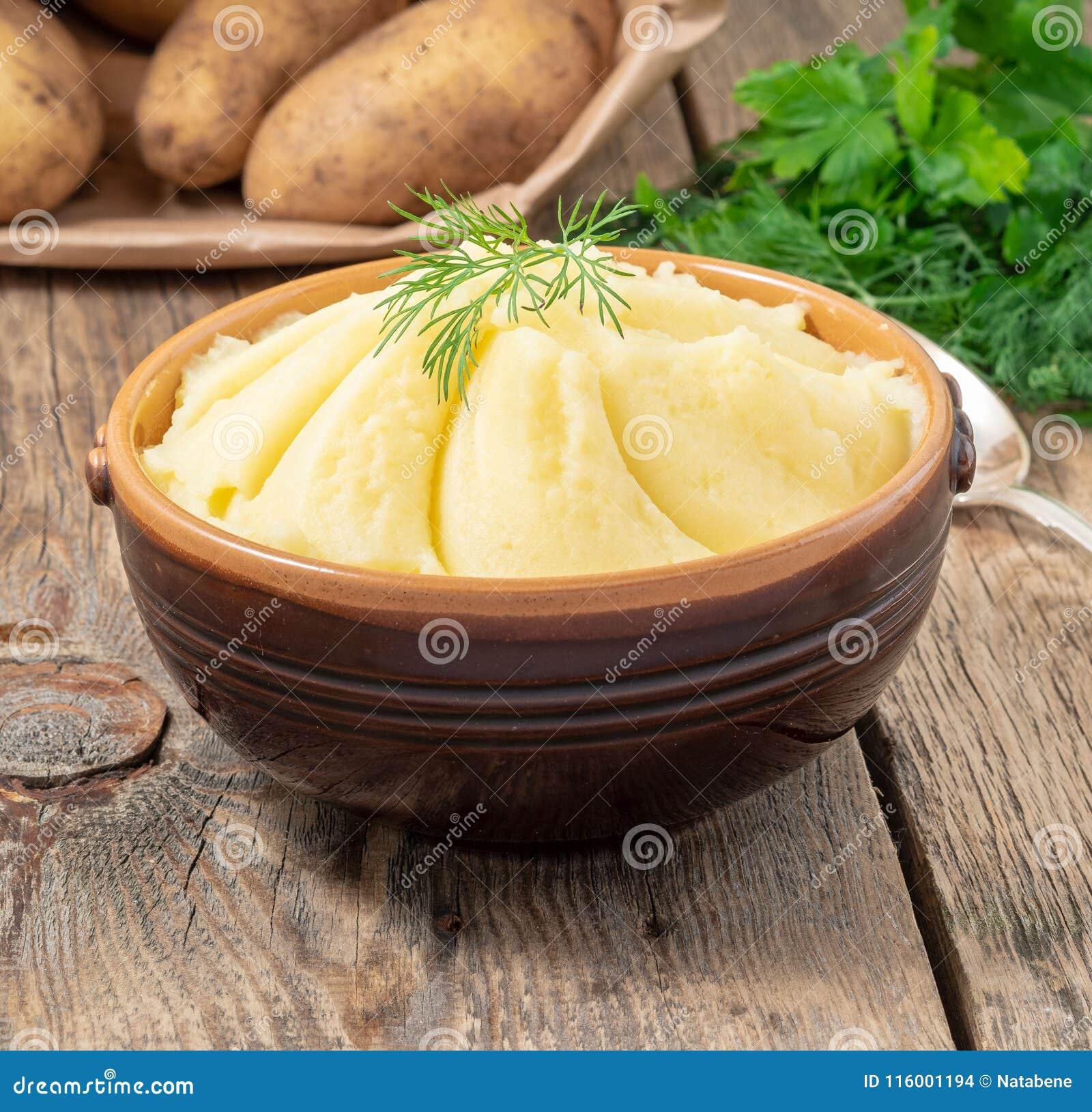Mosade potatisar, kokaad puré i brun bunke på mörk trälantlig bakgrund, sidosikt