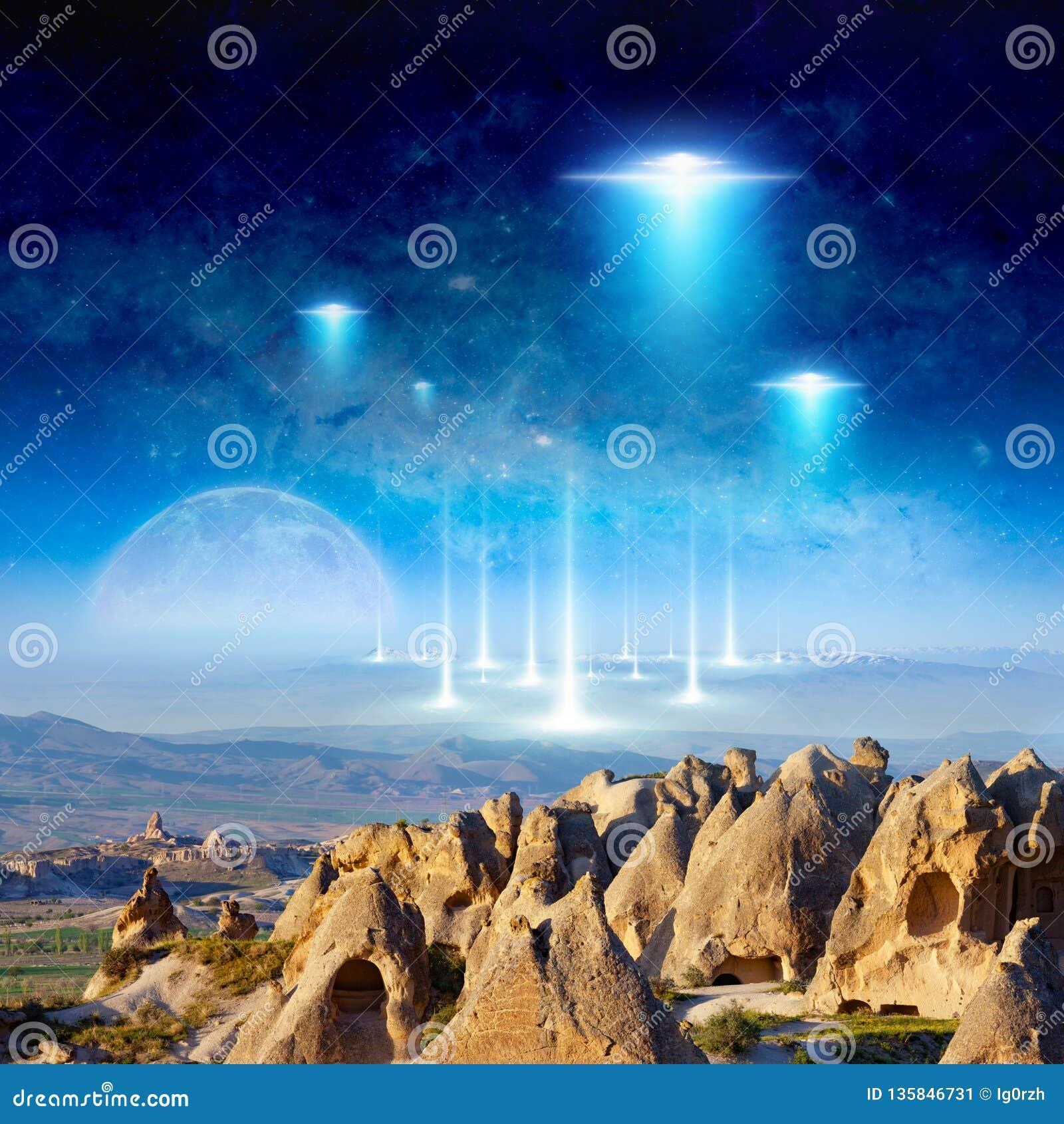 Mosca de la nave espacial de los extranjeros de Eextraterrestrial sobre terreno surrealista