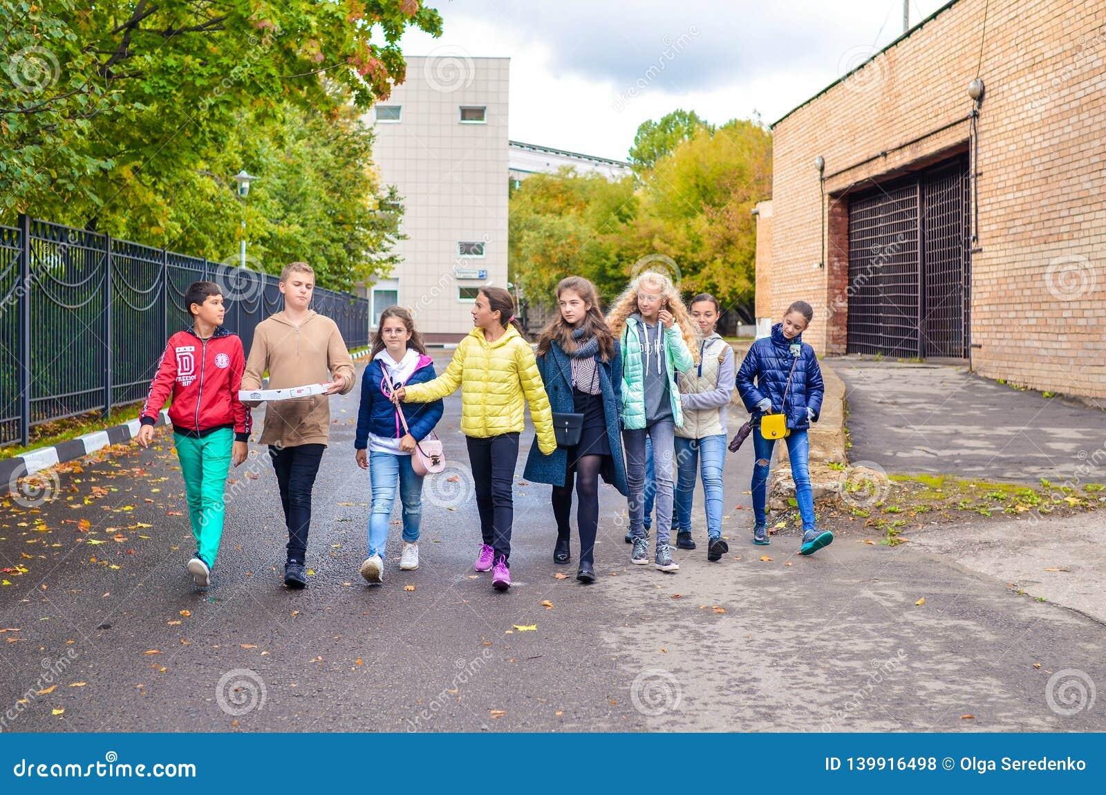 Mosca, Russia, il 23 settembre 2018 Gruppo di giovani ragazzi e di ragazze che parlano e che camminano giù la strada