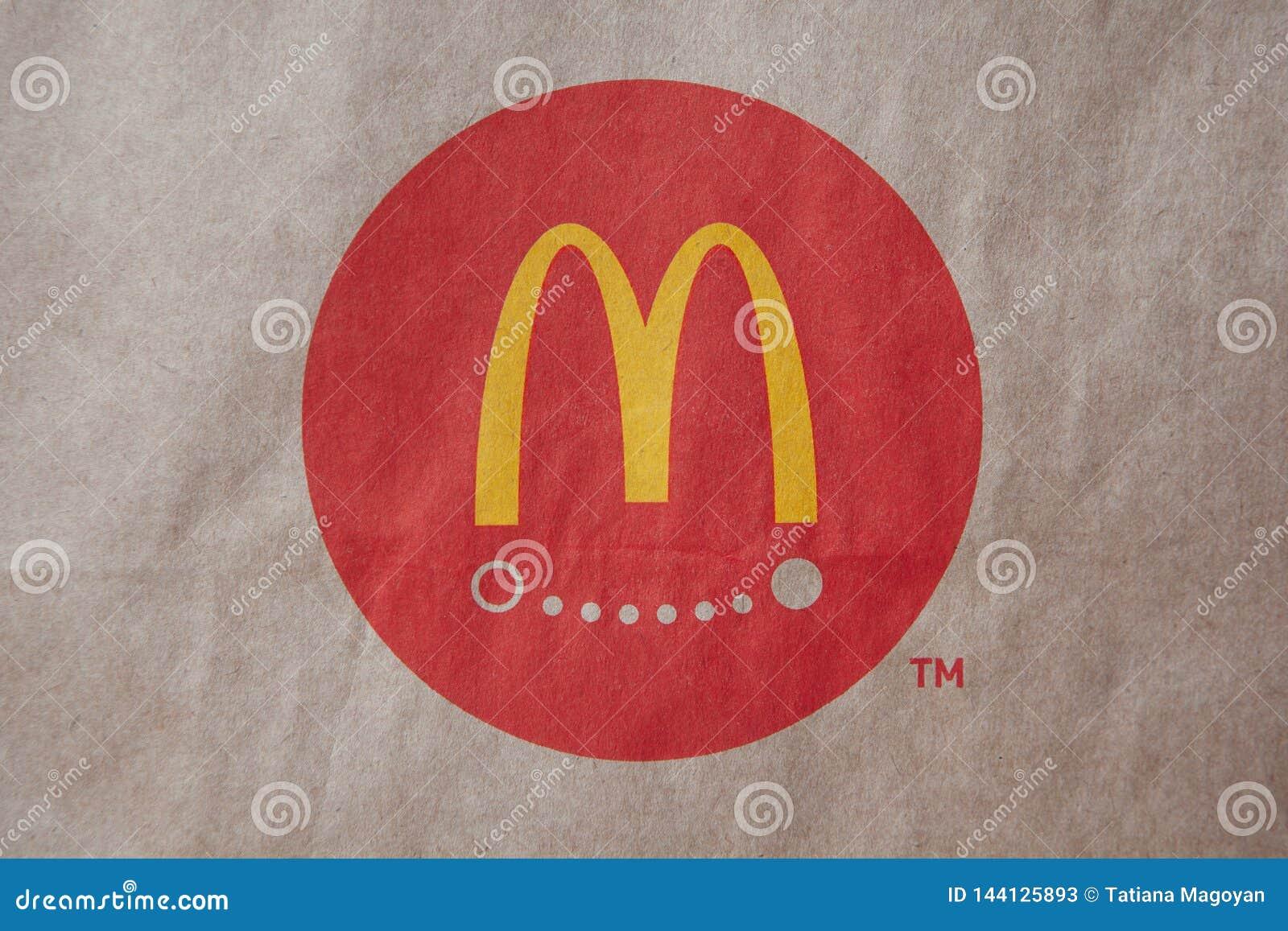 Moscou, Rússia - 6 de abril de 2019: Entrega do alimento do logotipo de mcdonald no fundo marrom do papel do ofício Close-up Vist