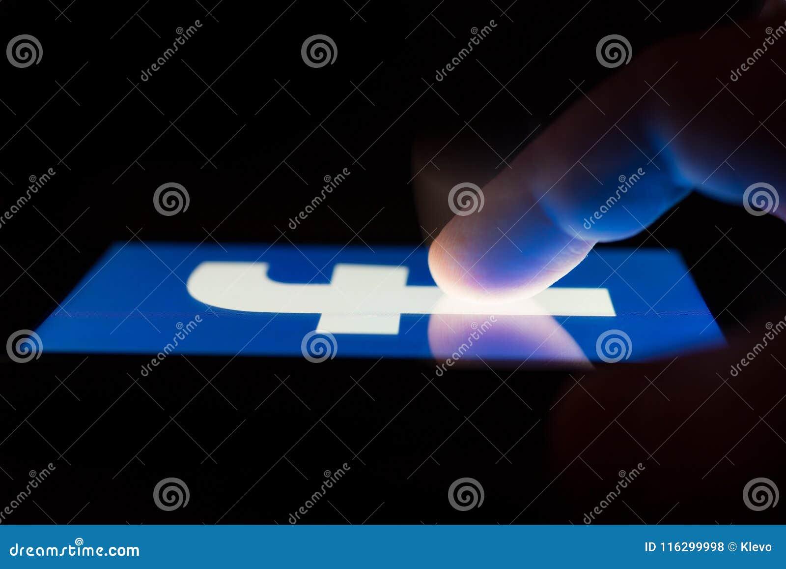 MOSCOU, RÚSSIA - 9 de maio de 2018: Um smartphone que encontra-se em uma tabela no escuro, indicando o logotipo de Facebook