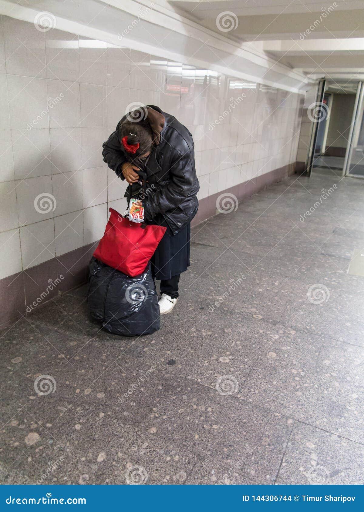 Moscou, Rússia - 9/20/2015: A senhora desabrigada está escondendo sua cara que finge classificar o pacote entre a estrada de ferr