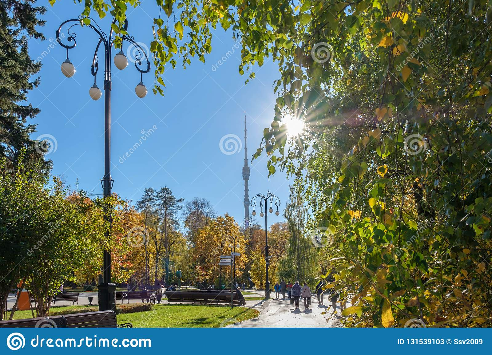 Moscow - October 12, 2018: Beautiful sunny day in Ostankino park. People walk in autumn park. The beam of sun light make their way