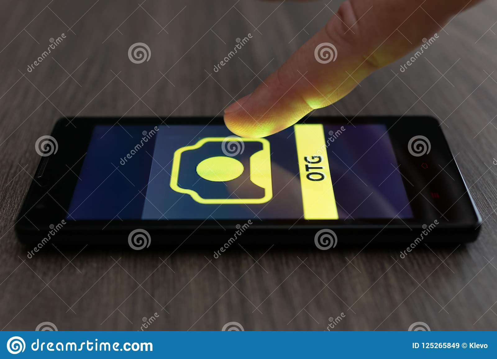 MOSCOW, RUSSIA - August 19, 2018: Smartphone on table displaying logo of 123RF app. Finger above touch screen. Microstock OTG