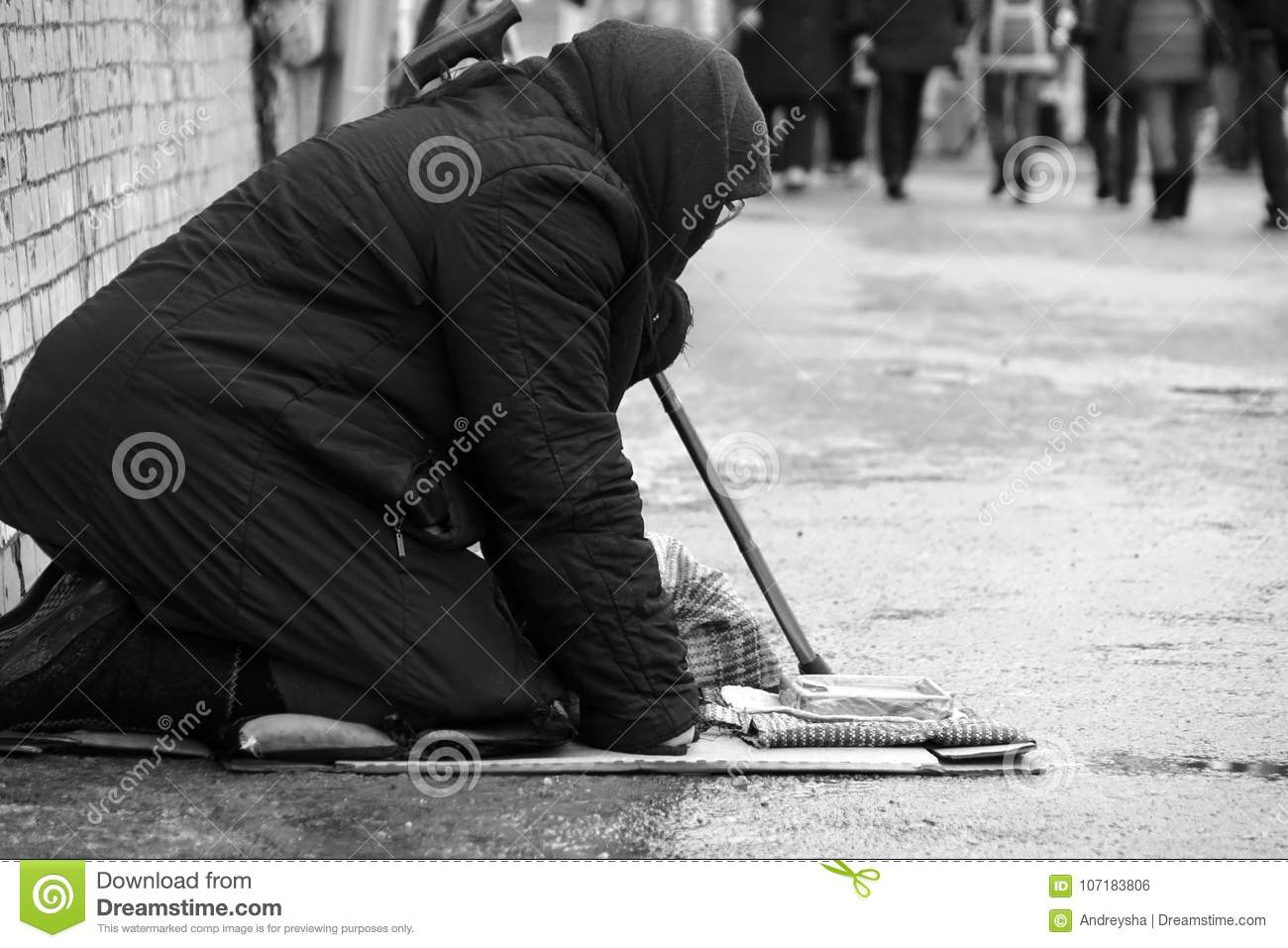 January 2018 sad homeless woman sitting on the street people passing by black and white photo