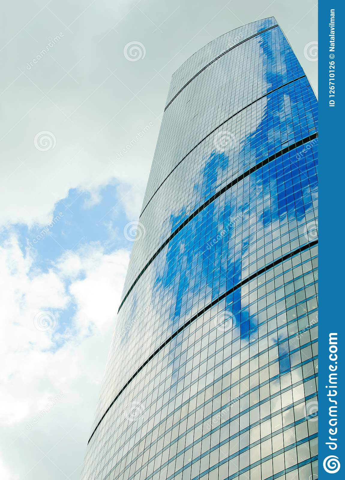 Wall of a skyscraper with mirror glass against a sky with clouds. Vertical photography.
