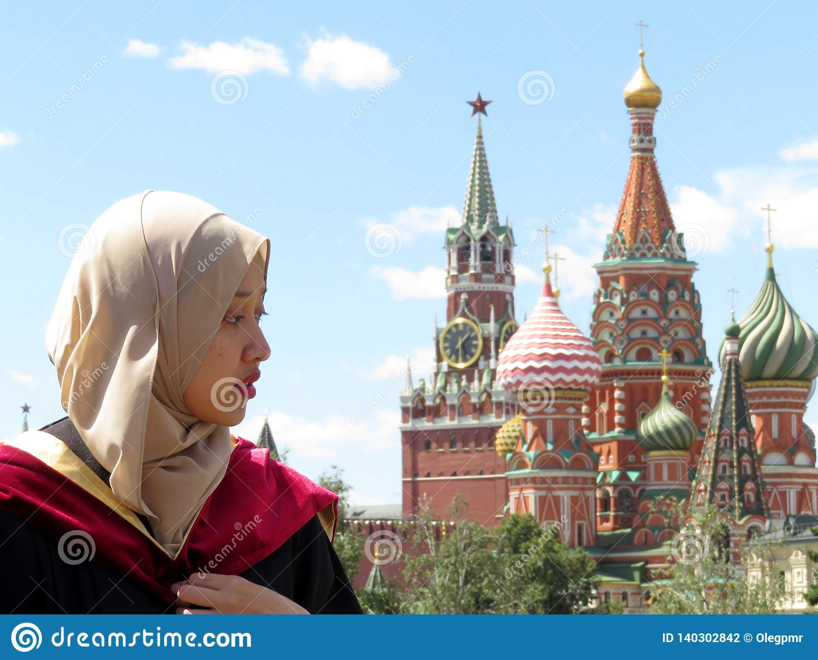 Muslim girl in hijab on background of the Moscow Kremlin and St. Basil`s Cathedral