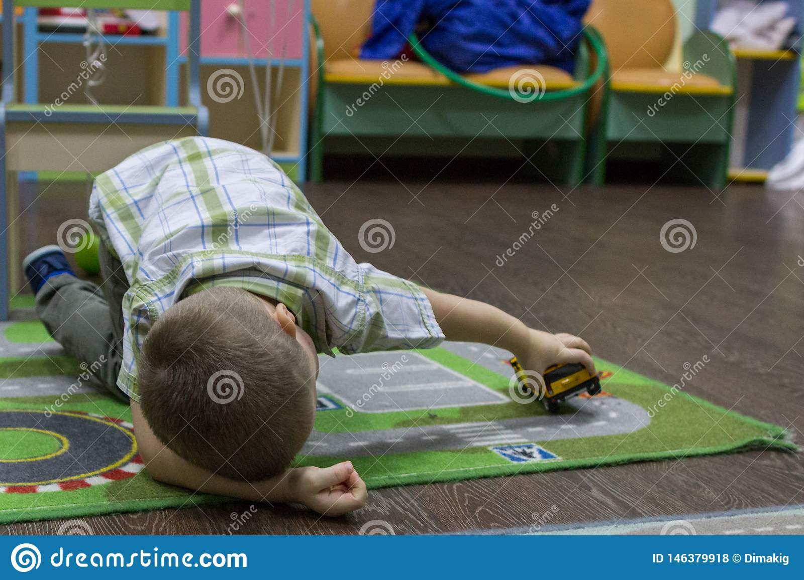 Little boy playing cars on the carpet. Entertainment of childhood.